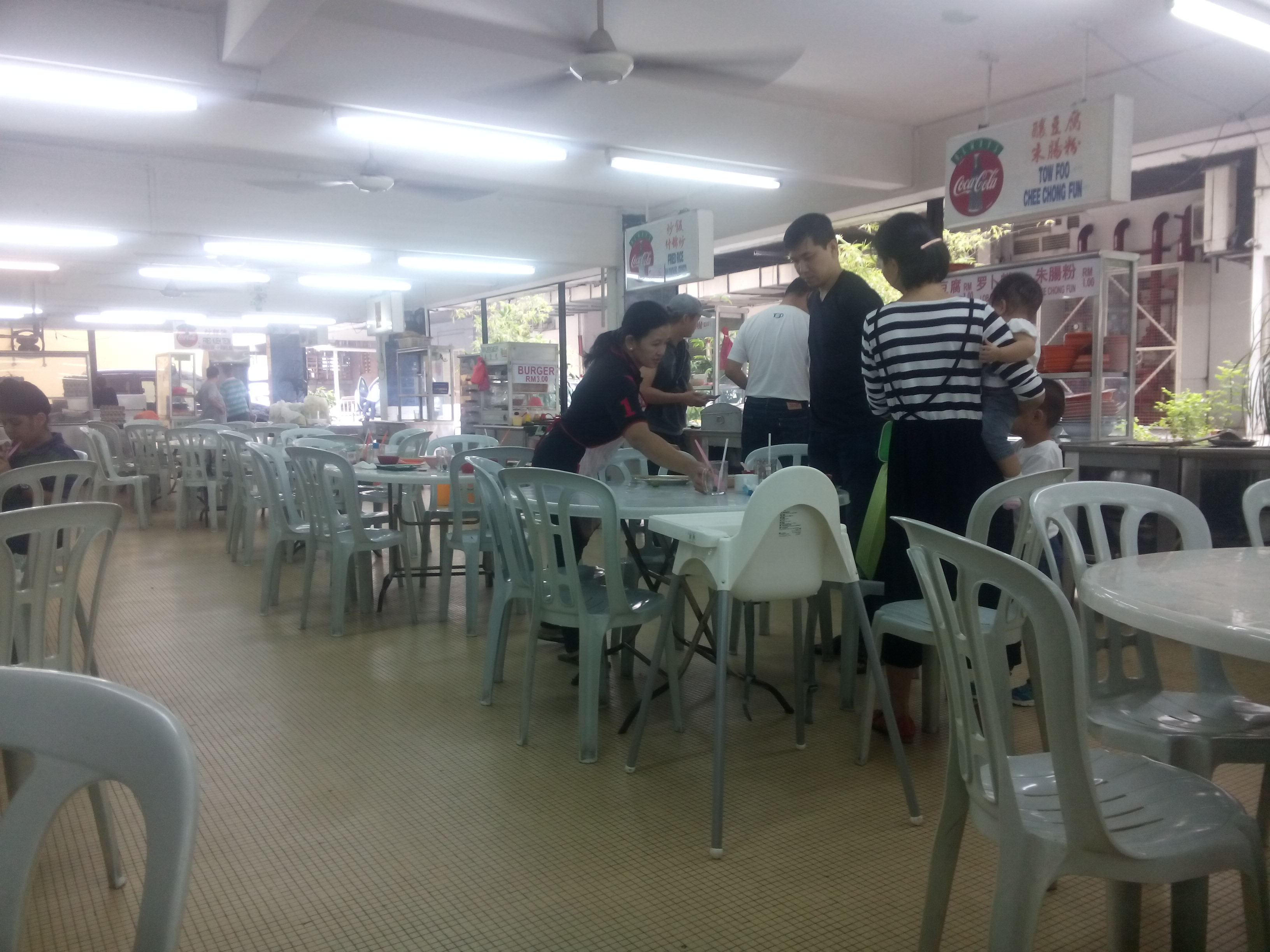 Inside Blue Boy: plastic tables and chairs, people, food stalls