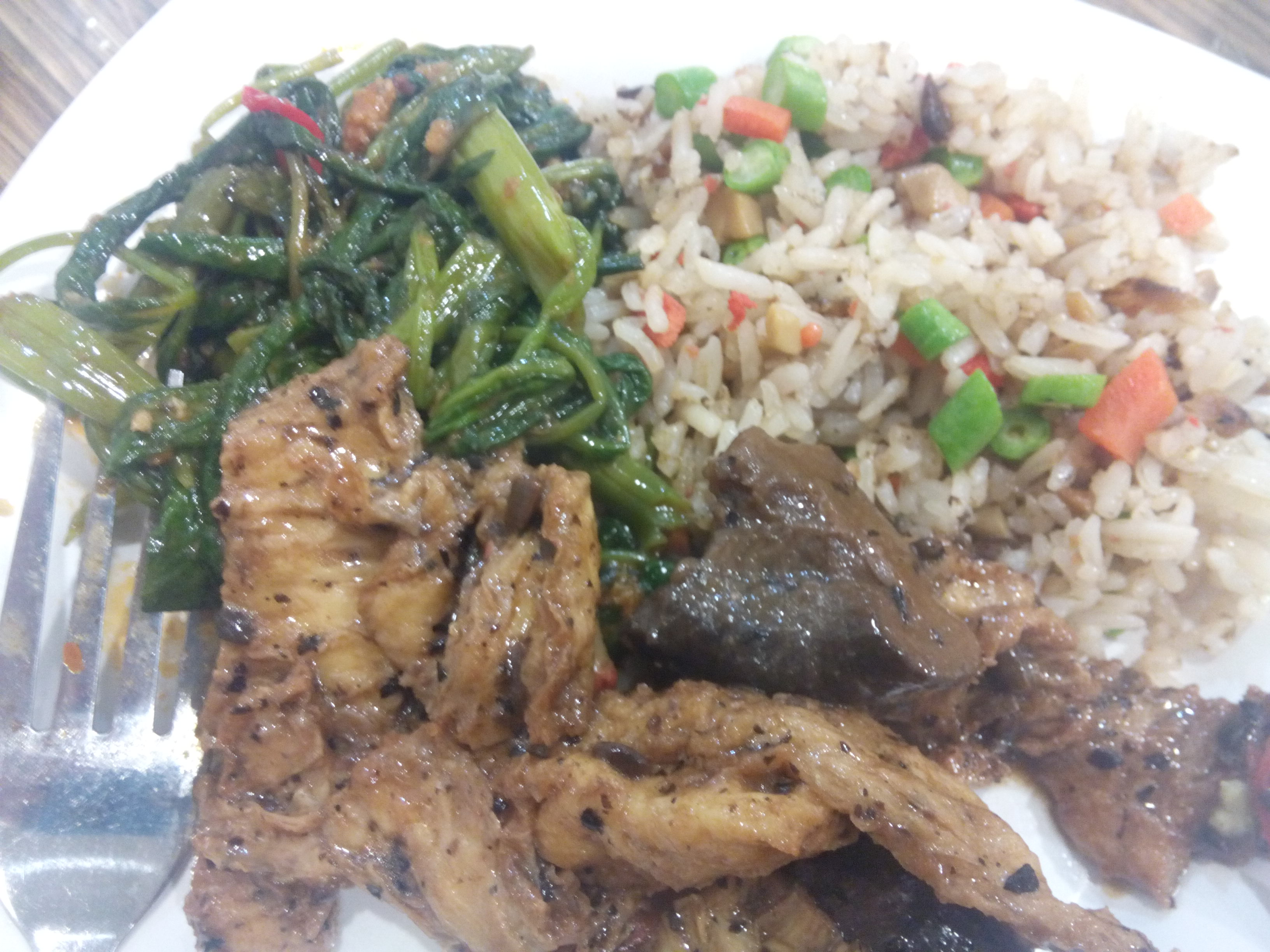 One plate with green leafy vegetables, fried rice, tofu in sauce