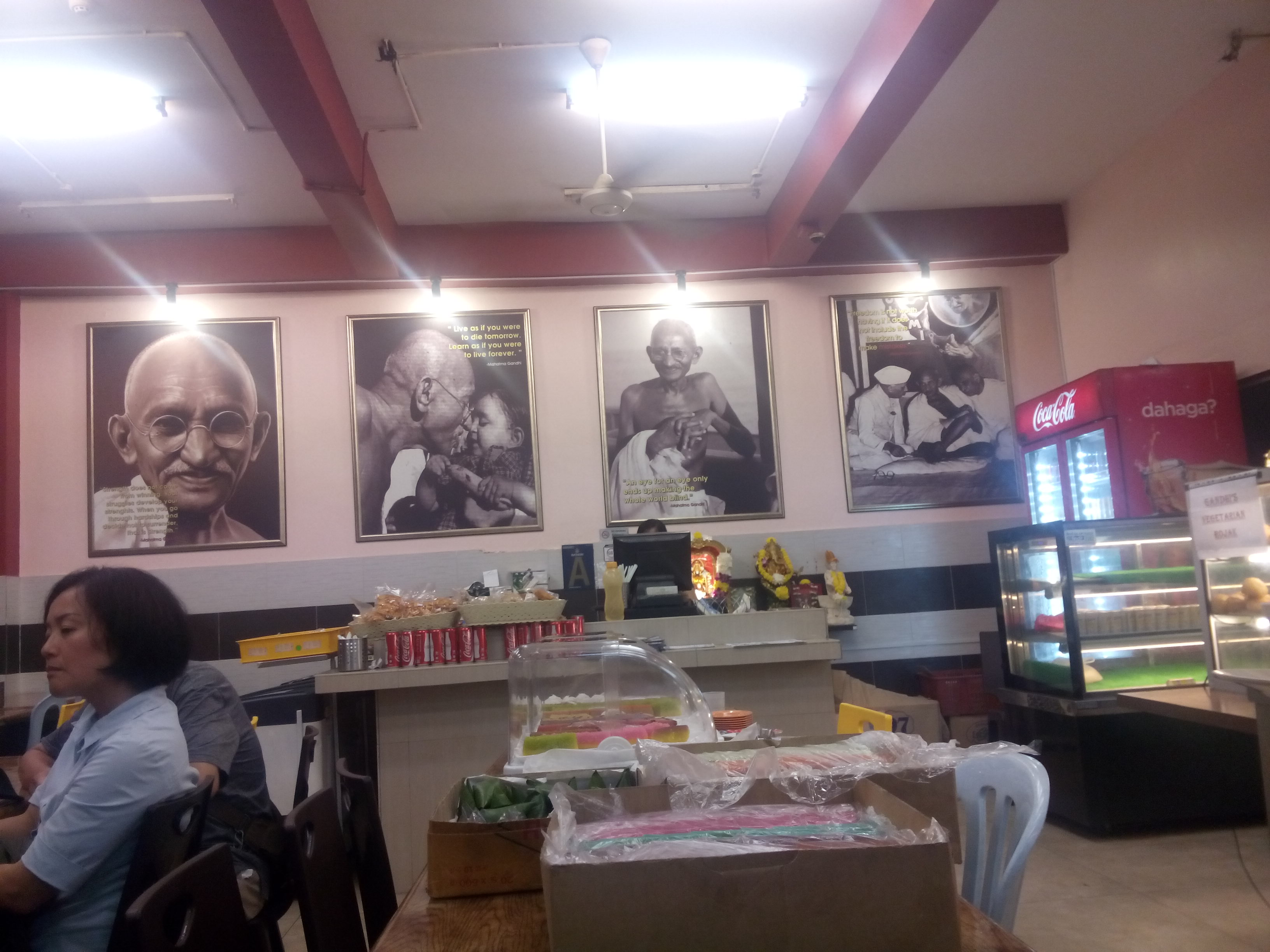 Gandhi's restaurant inside, tables, and photos of Gandhi on the walls