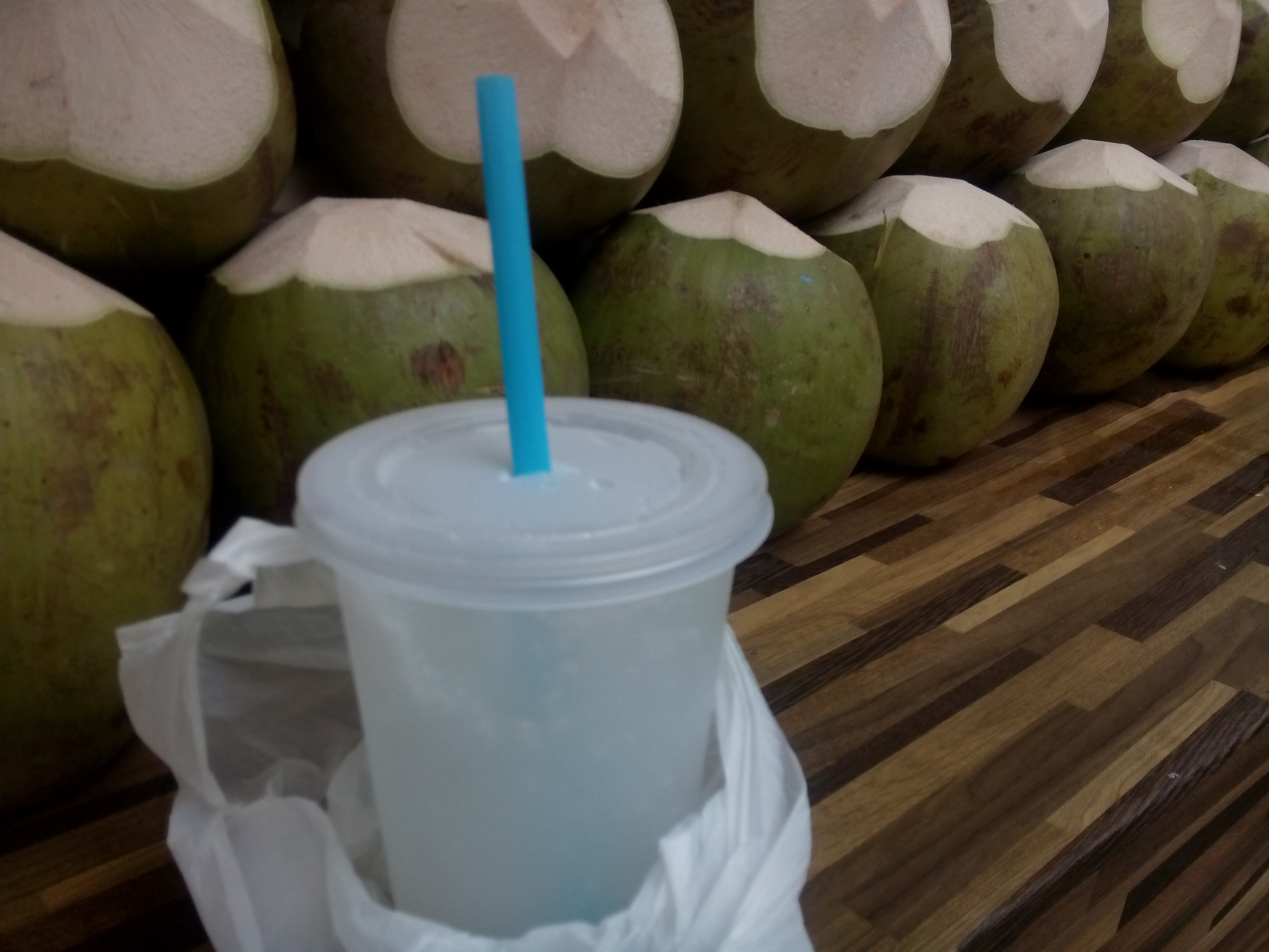 Coconut water in a take out cup, beside a stack of coconuts