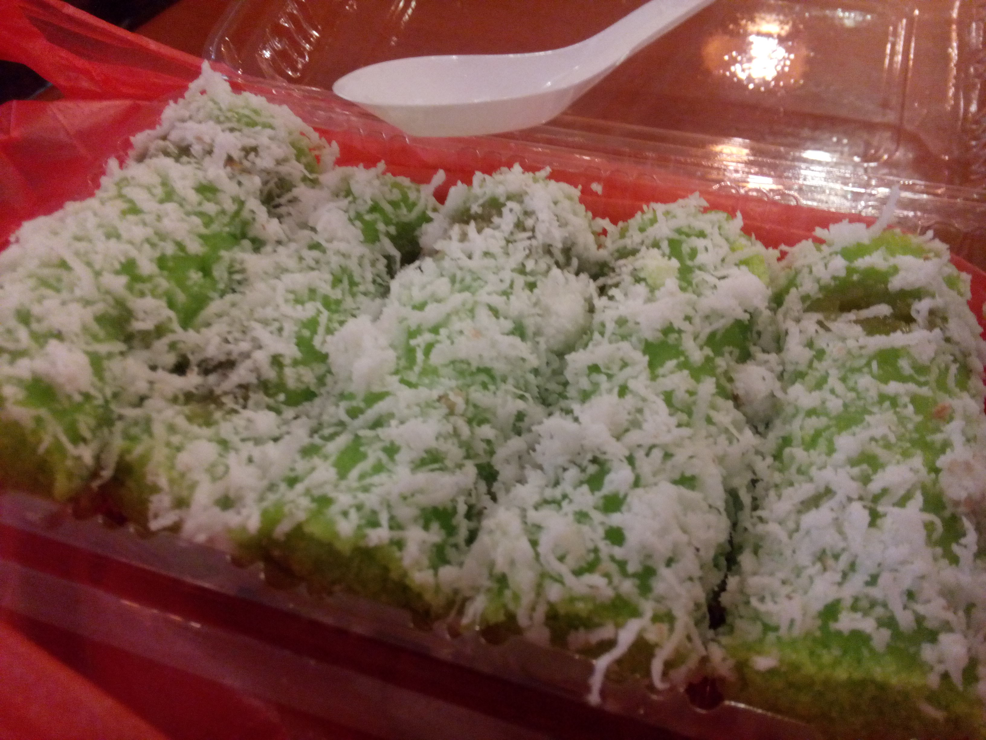 Green coconut covered spongy things in a plastic container