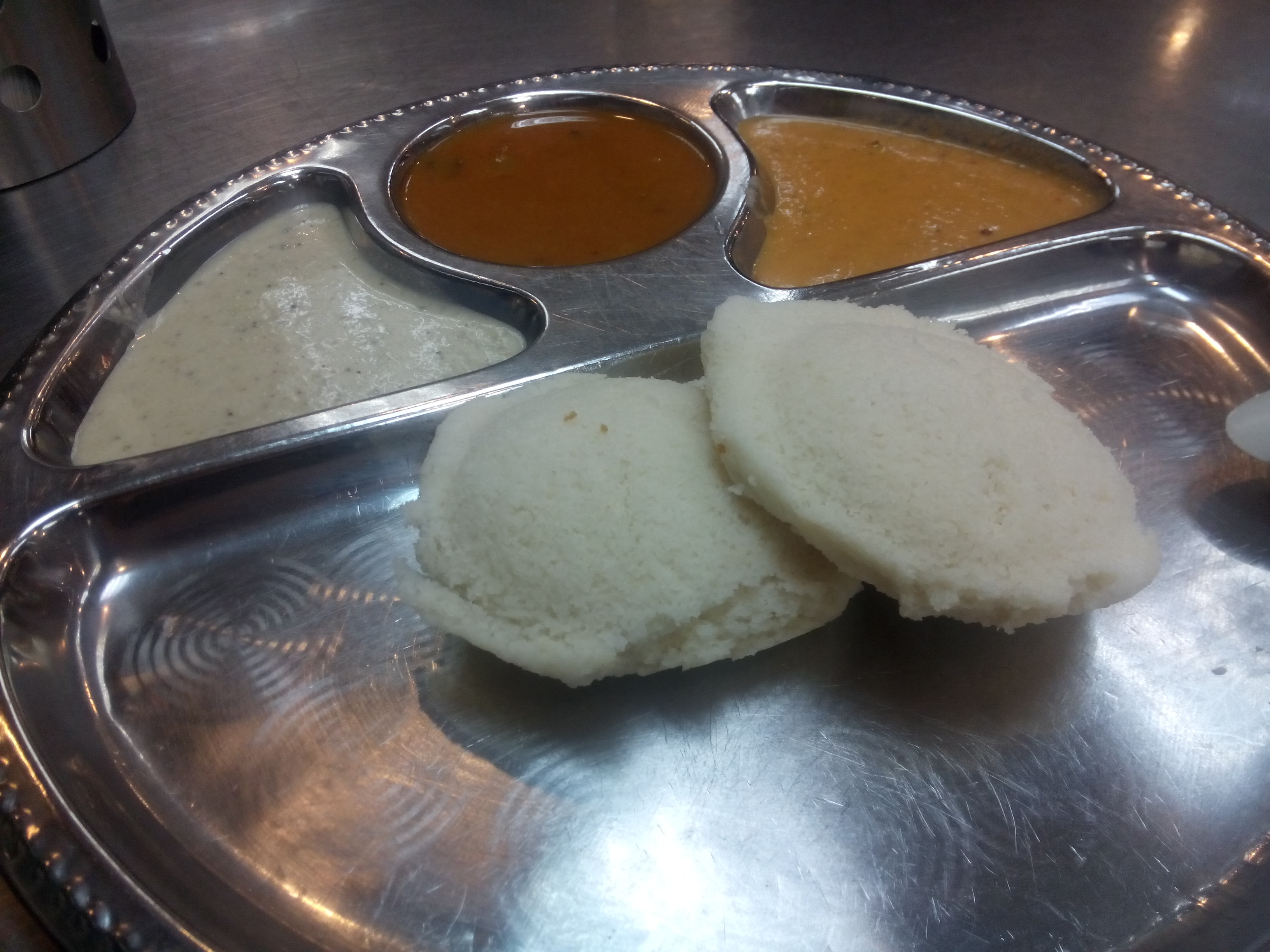 Rice bread (idli) and curries on a metal tray