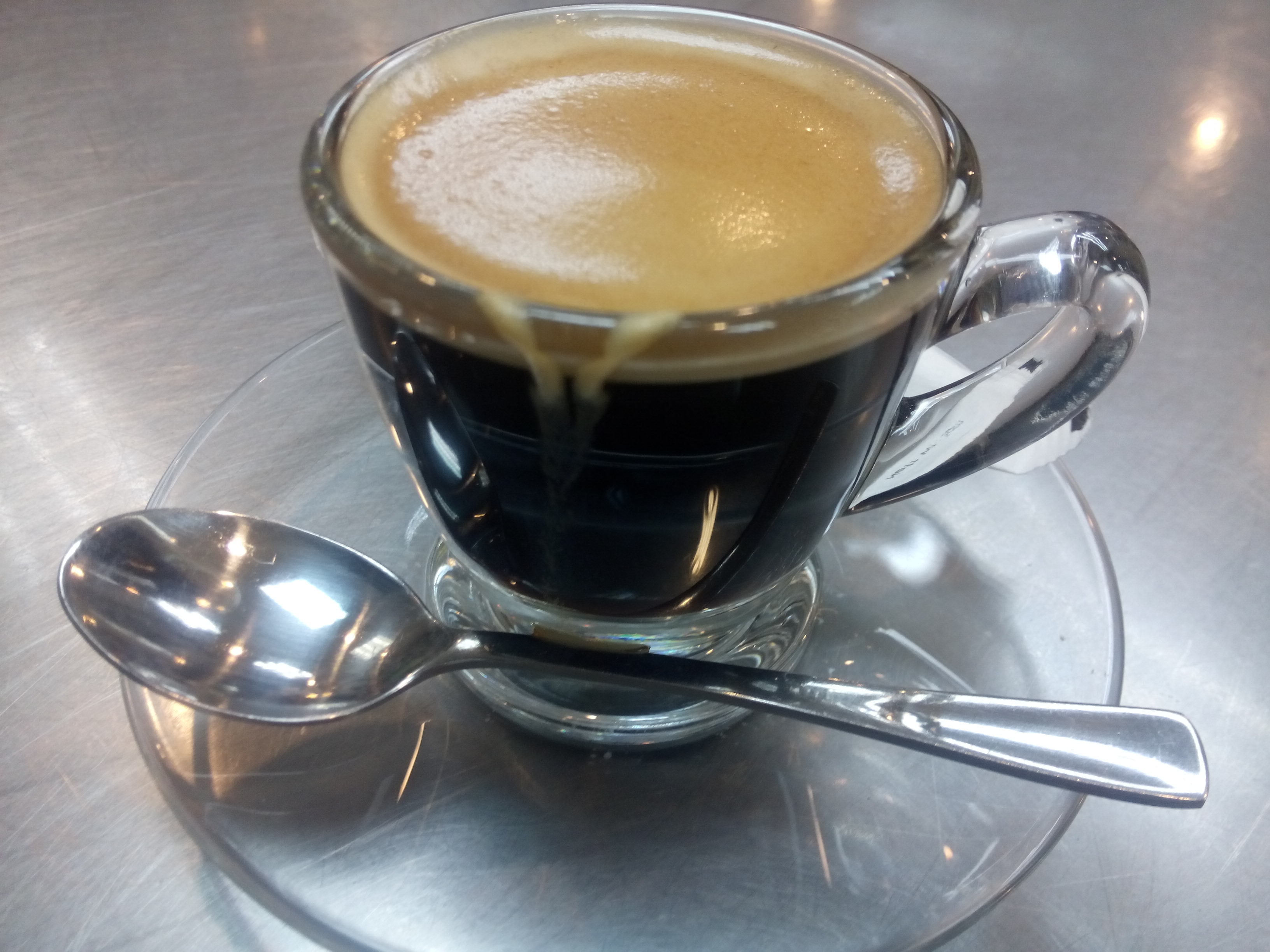 Foamy espresso in a glass cup with a shiny spoon