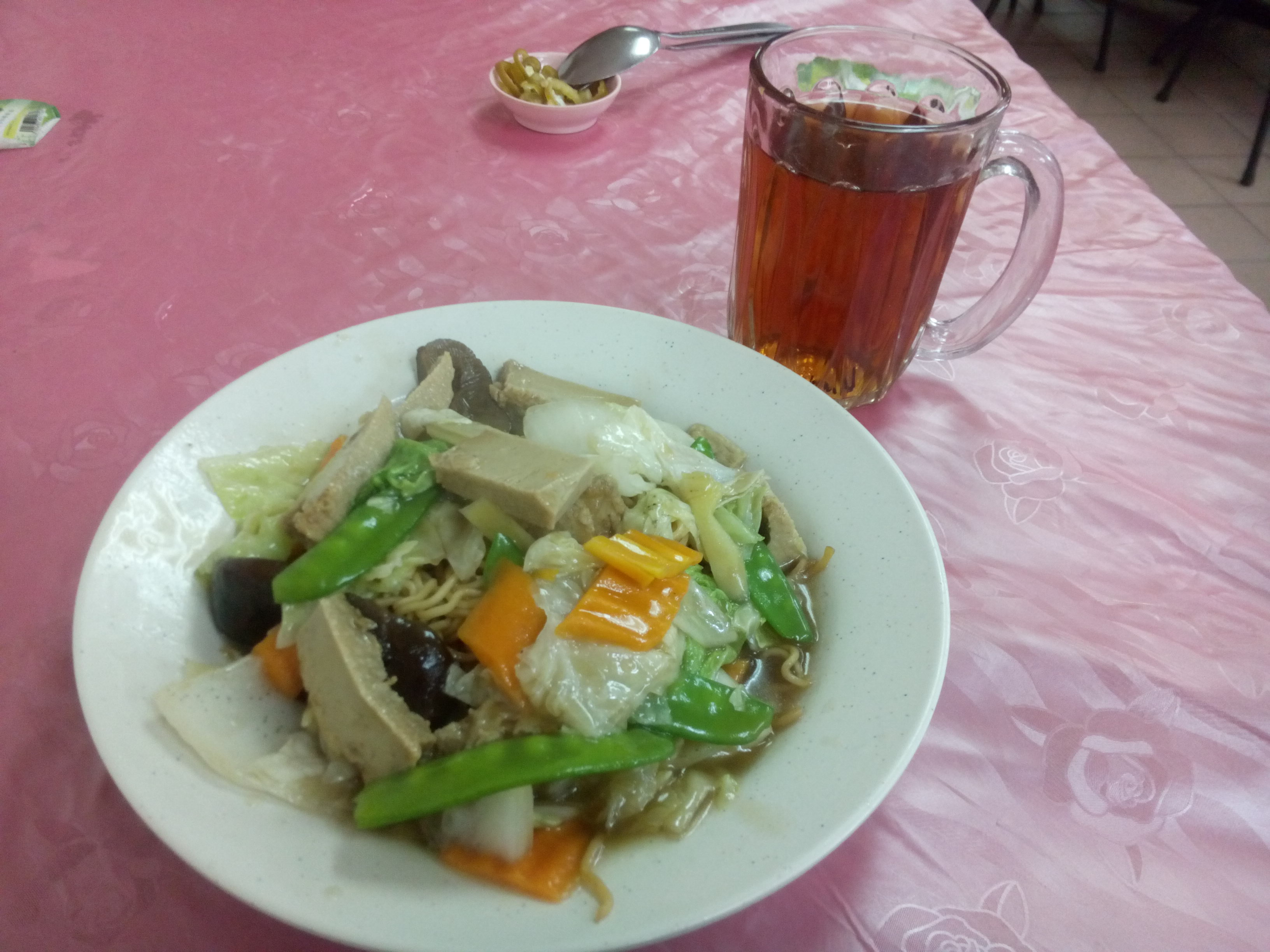 Noodles with vegetables and tofu, and tea in a glass mug