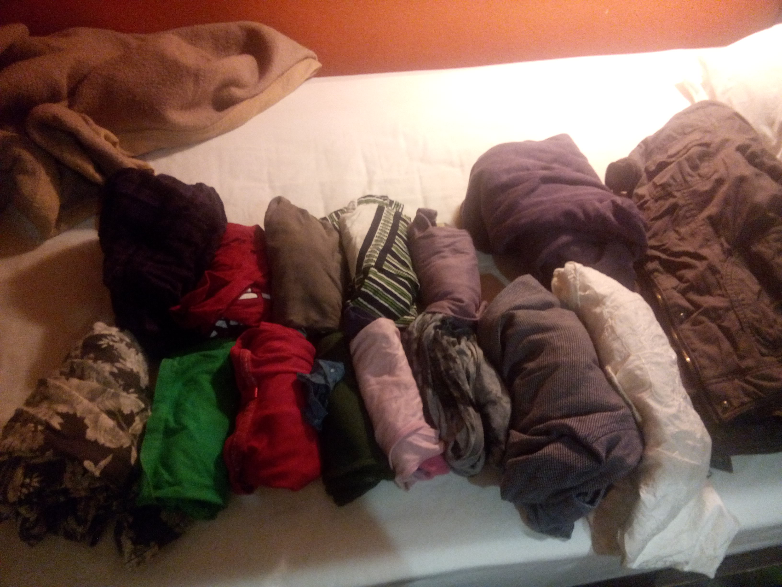 A pile of rolled up clothes on a bed
