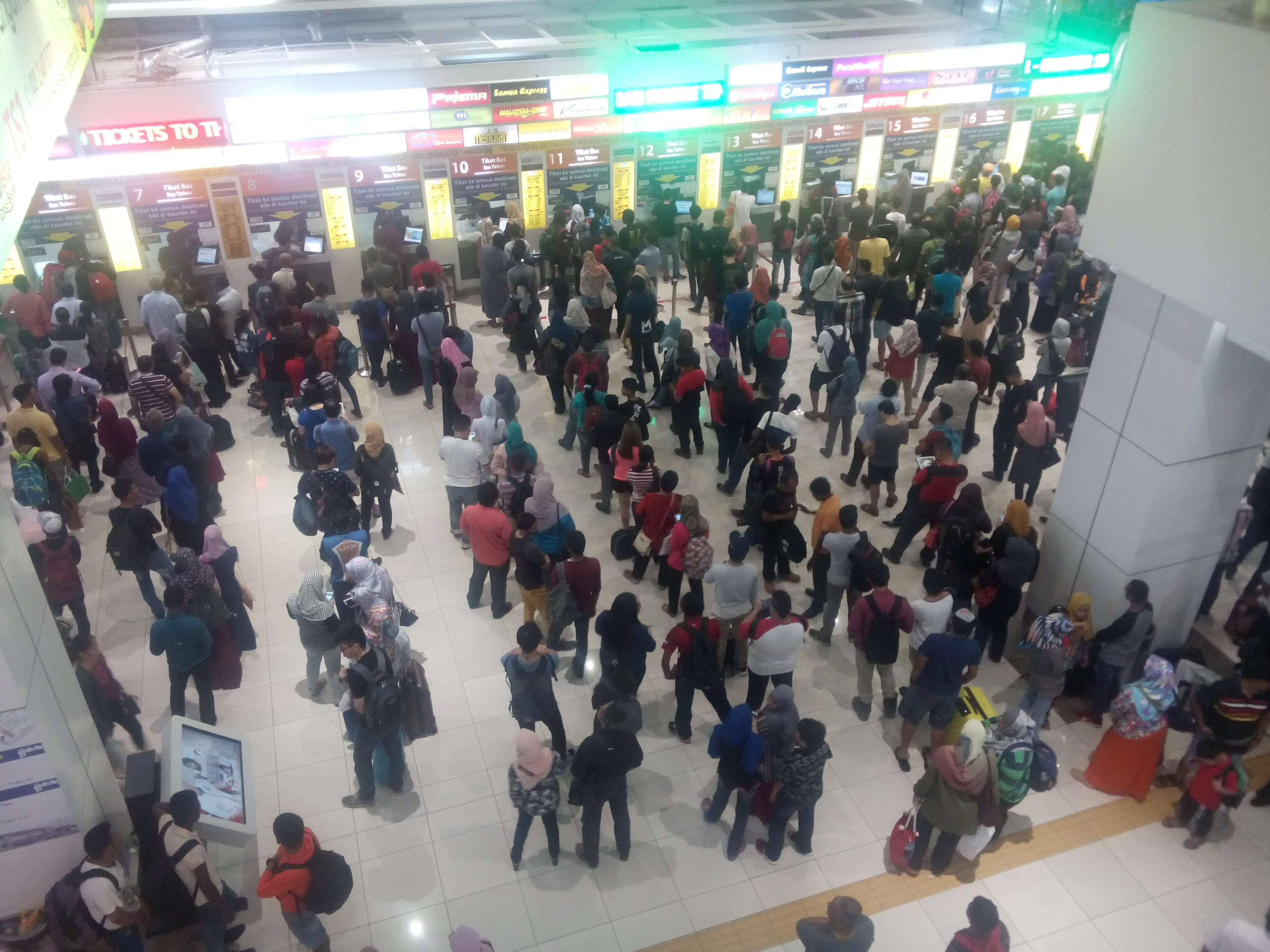 A crowd of people lining up for bus tickets, from above.