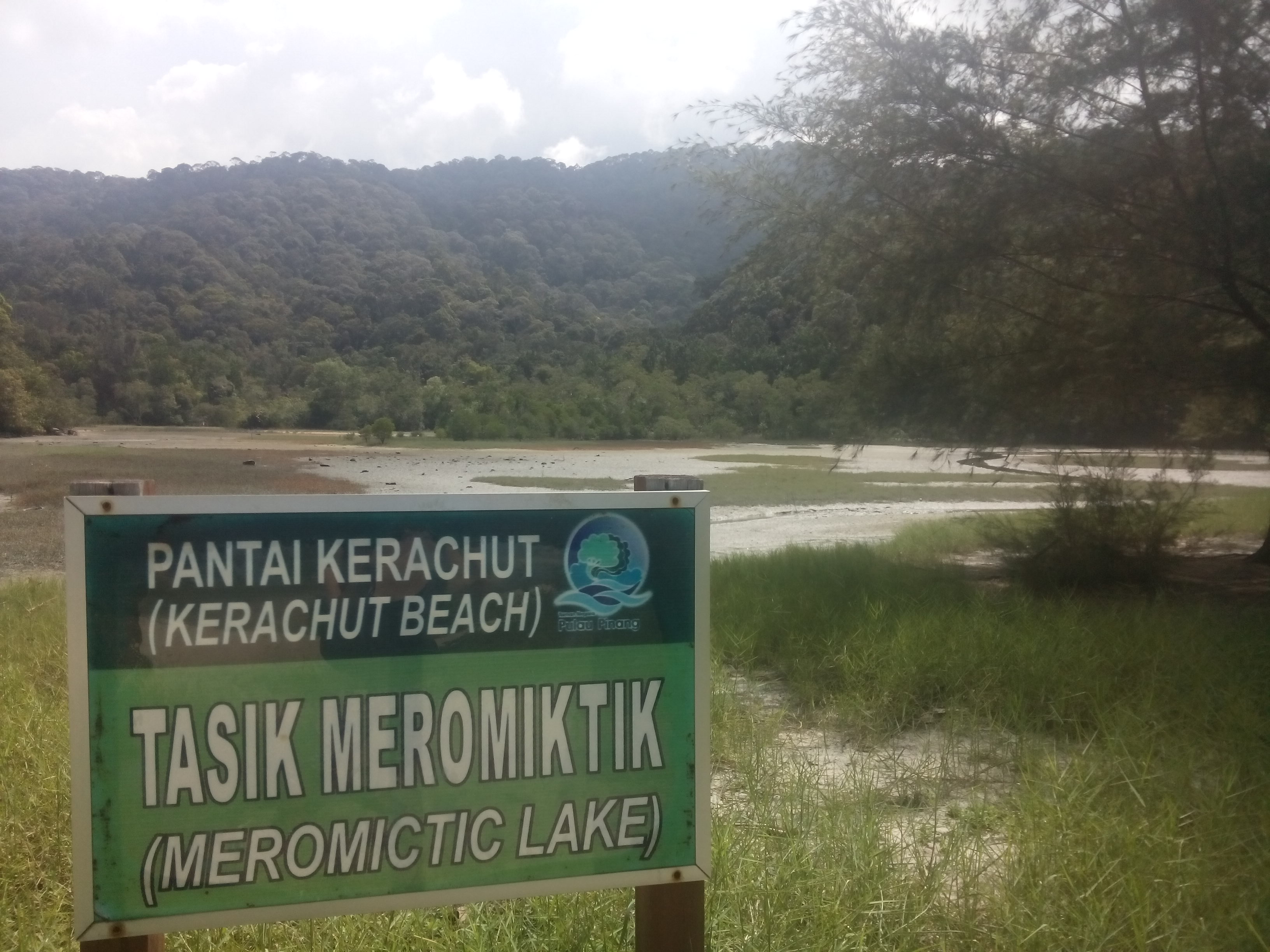 A mostly dry lake, with a sign reading 'Tasik Meromitik'
