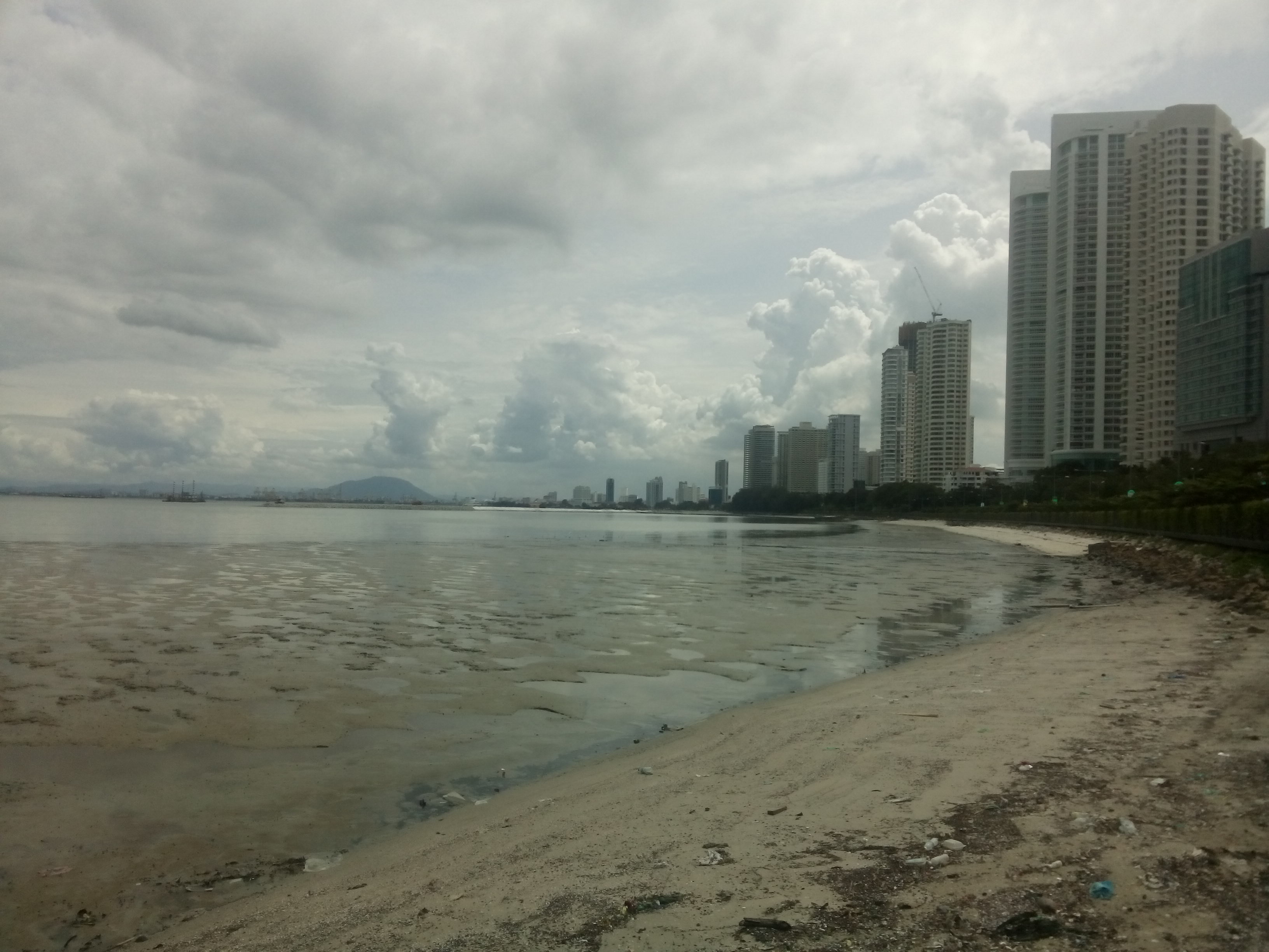 A view across the sea, with sand in the foreground and condos on the right