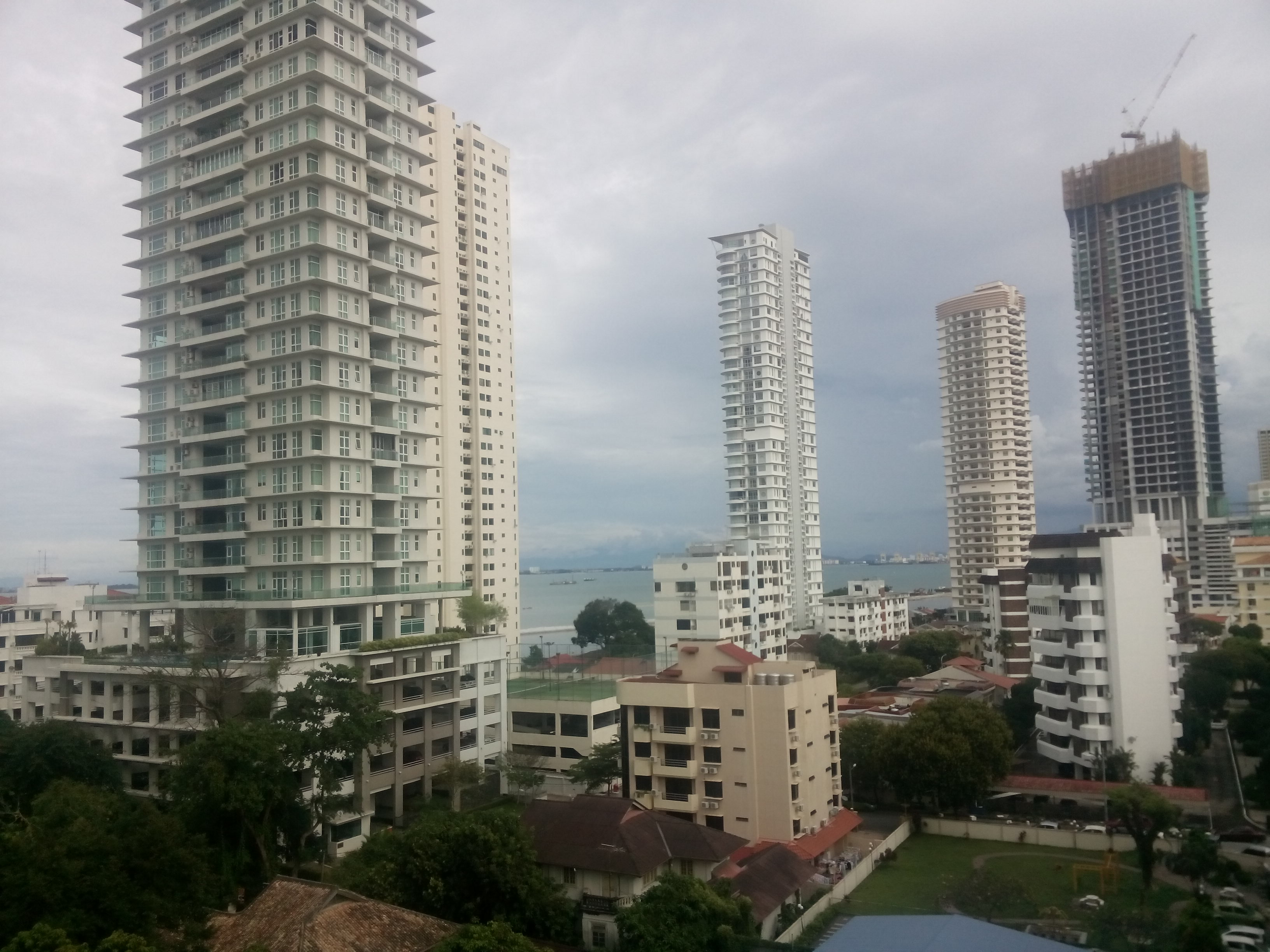 View of tall white condos and hotels, with the sea in the distance