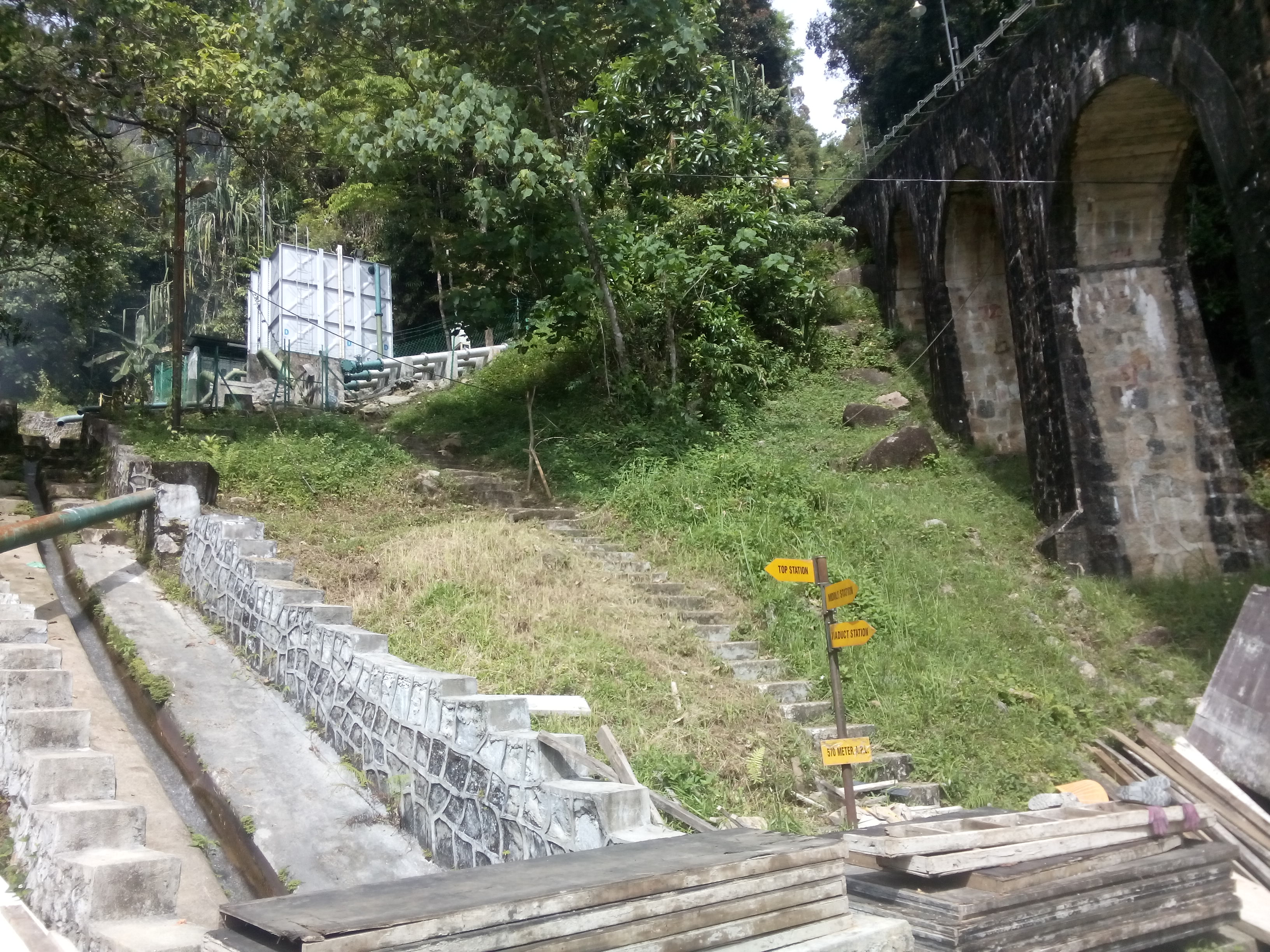 A railway bridge on the right, and steep steps amid greenery
