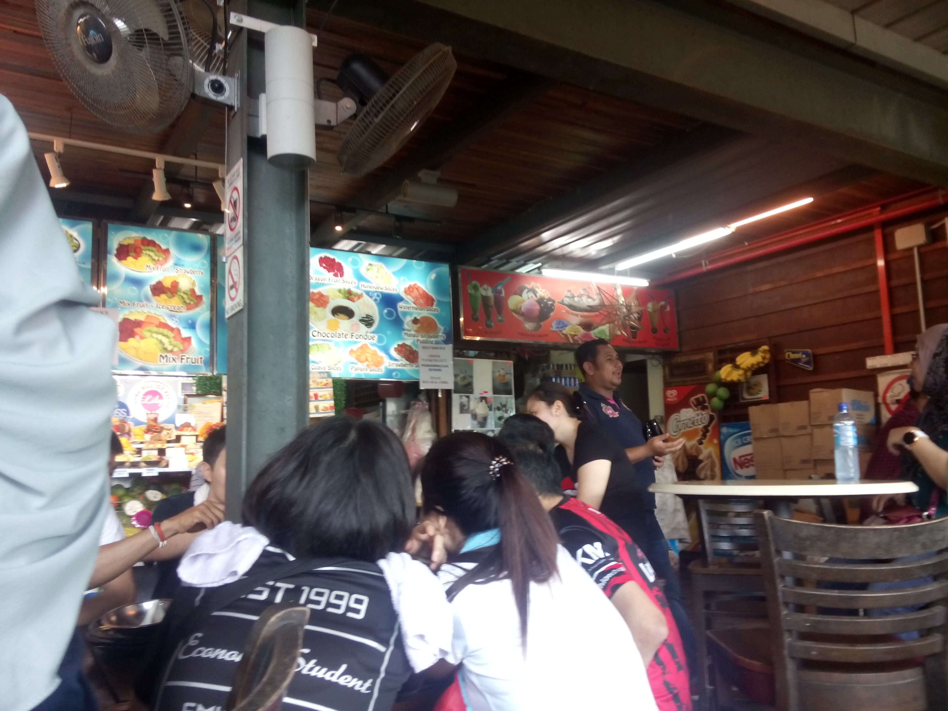 Food stands and people inside a wooden building