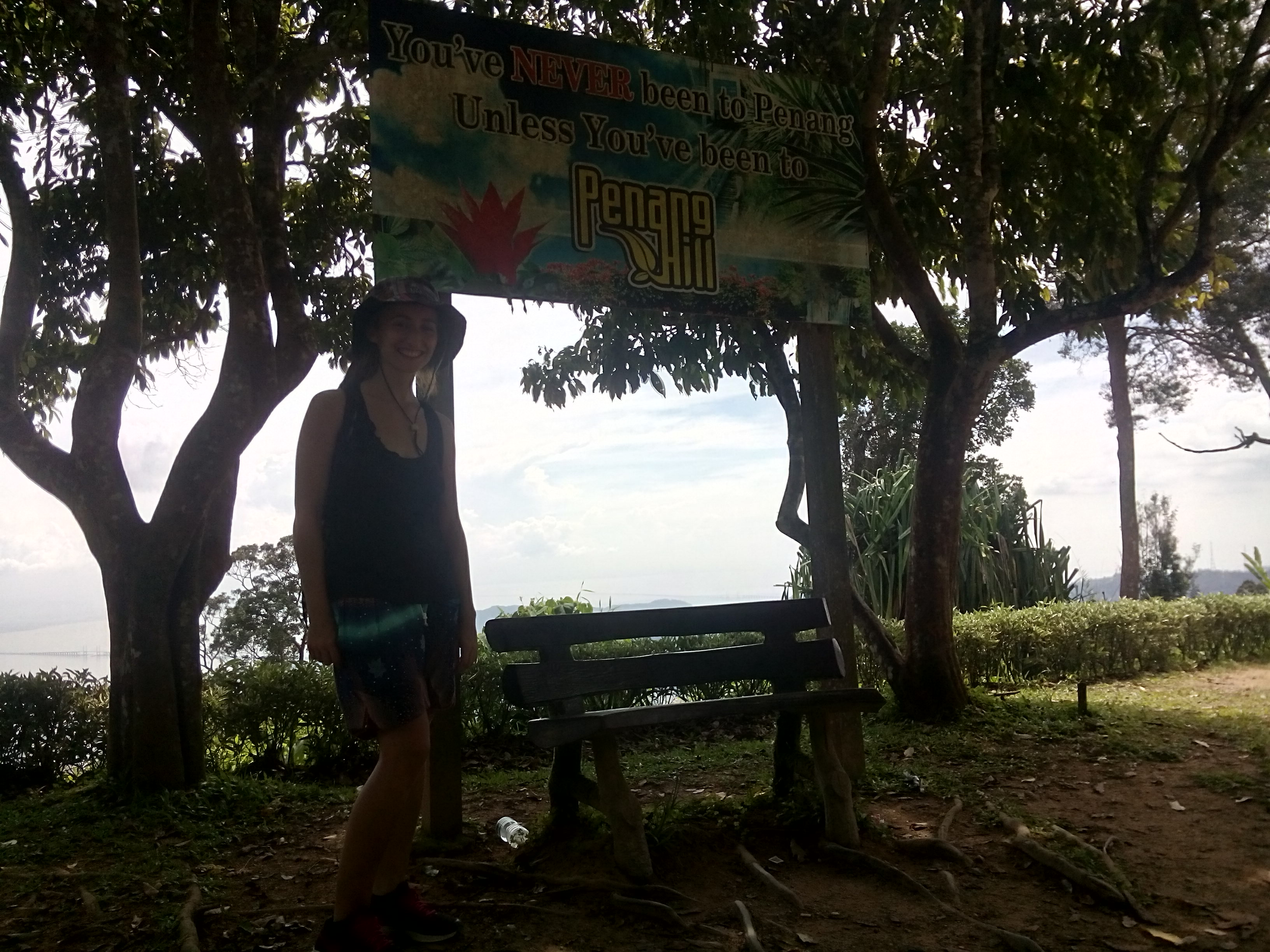 rhiaro in a hat in front of a bench and Penang Hill sign, with sea in the background