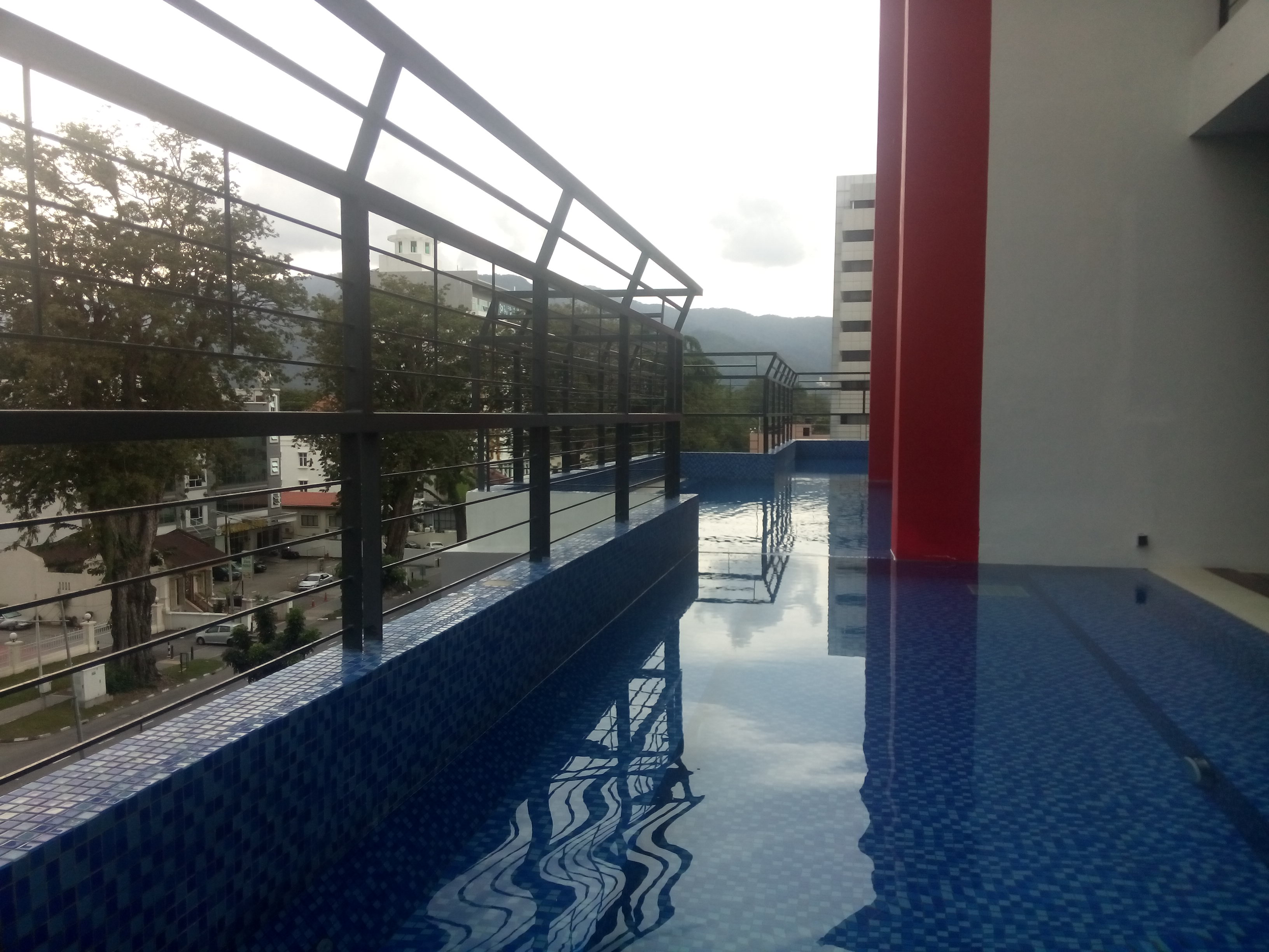 A pool on the edge of a building with mountains in the distance