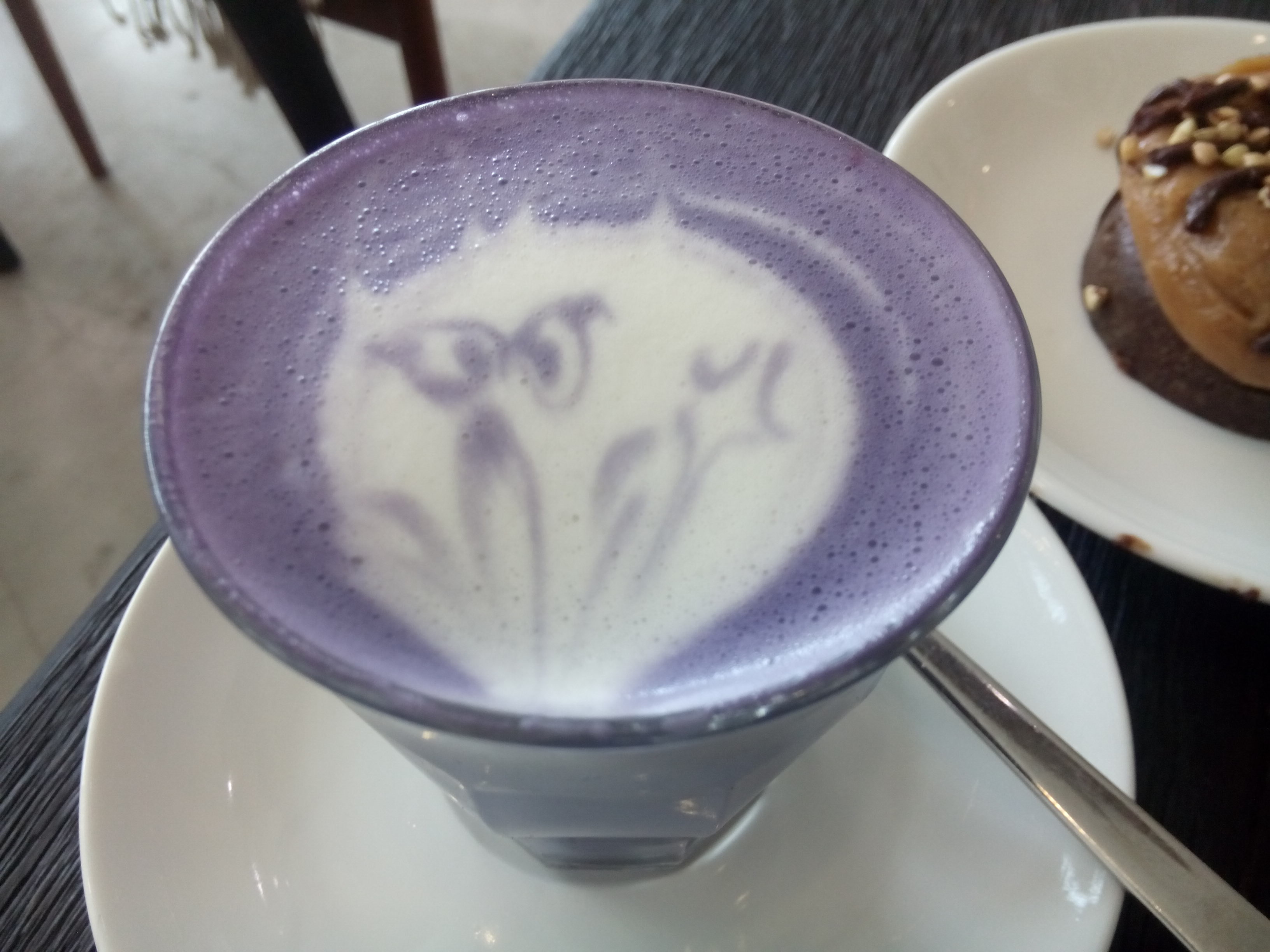 Purple drink with smudged cat latte art that now looks like a ghost
