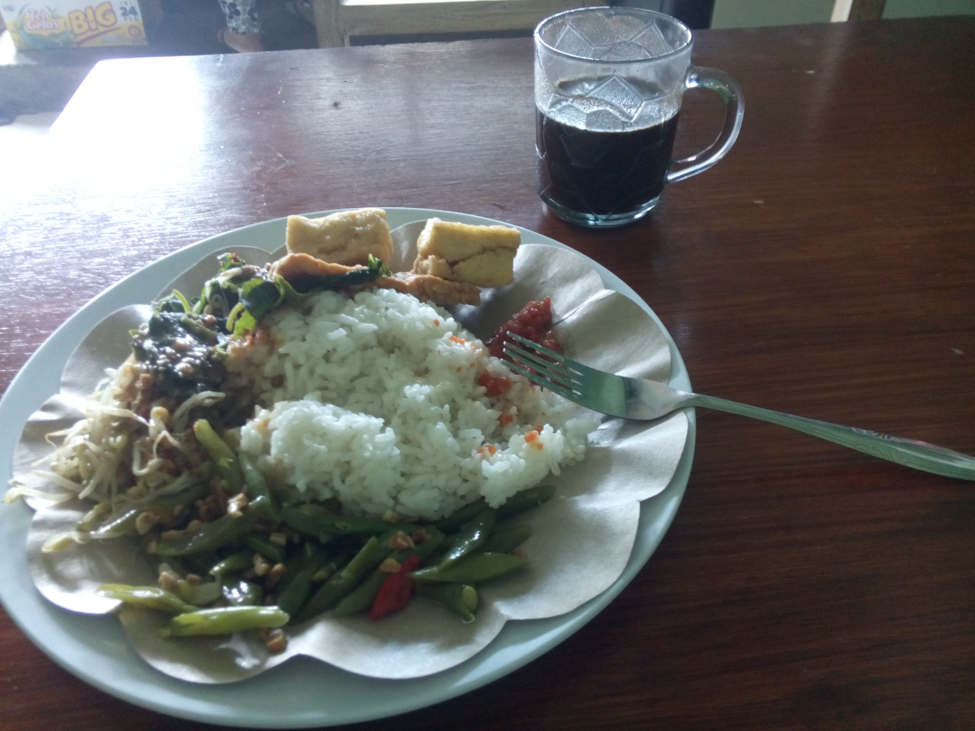 A plate of Indoenisan food, and coffee