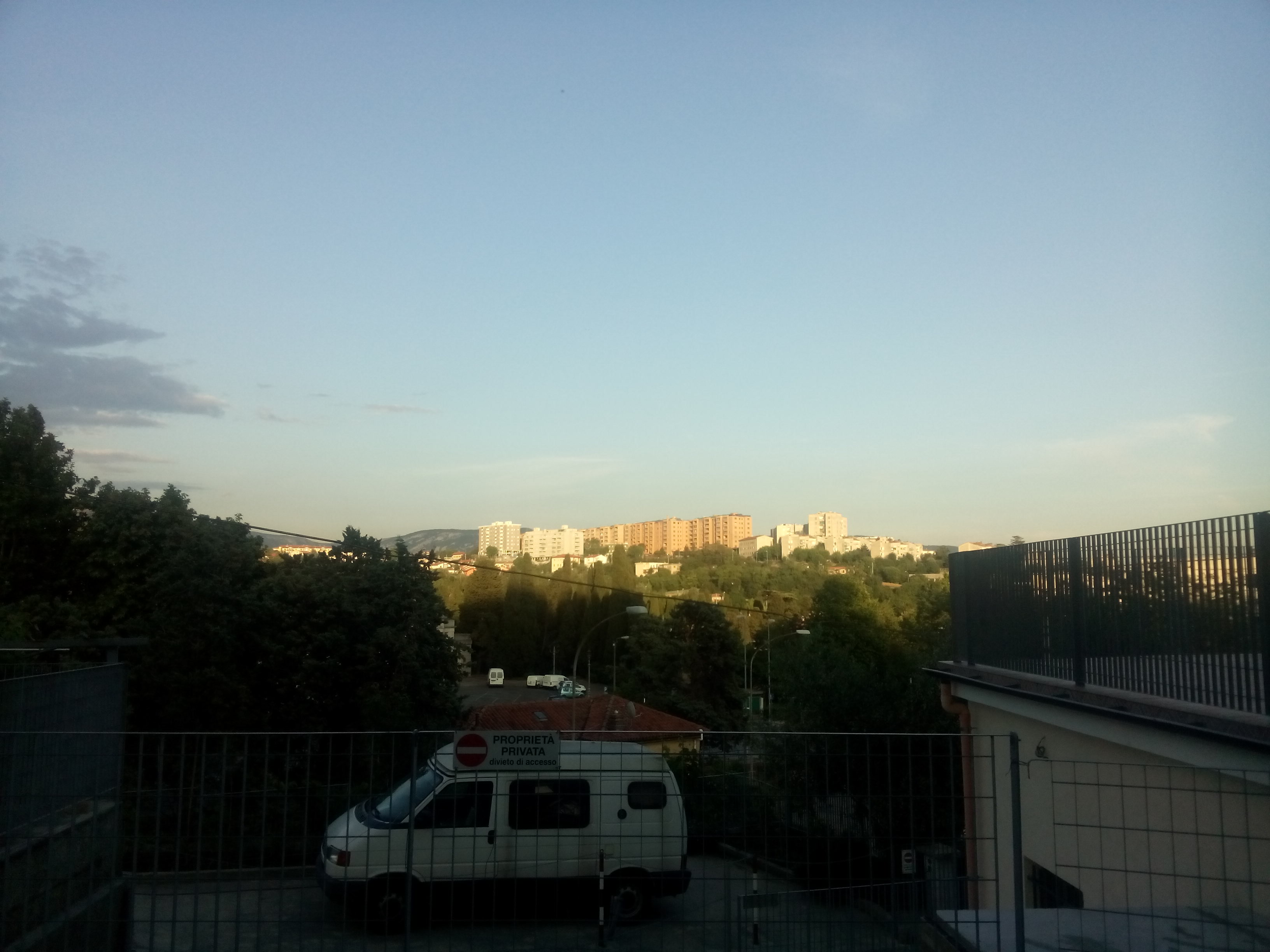 Blue sky, sun lighting up buildings on a distant hillside