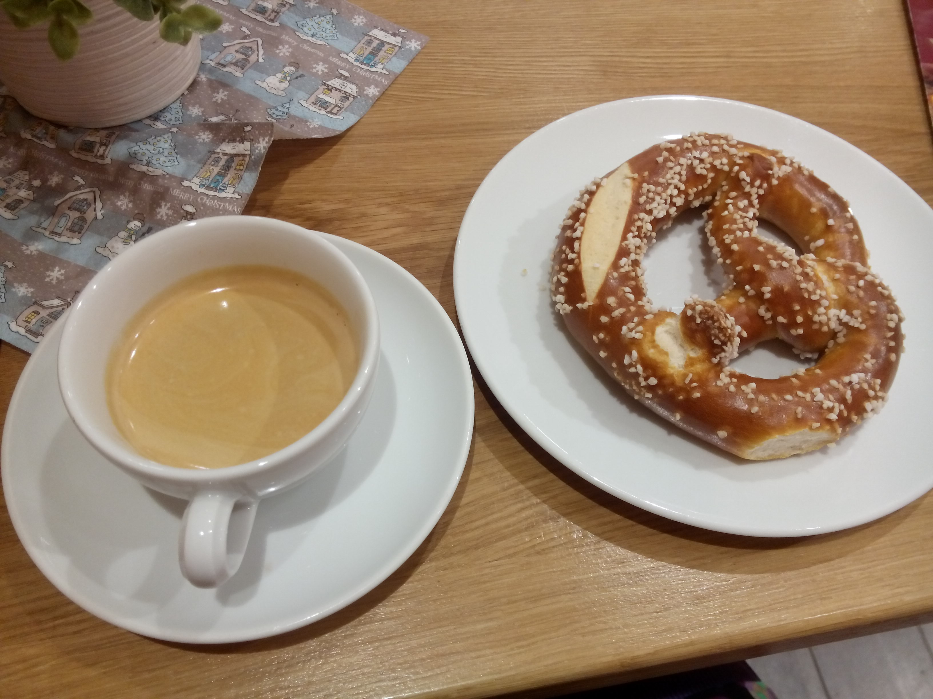 A coffee and a pretzel on a plate, on a wooden table with some blue and silver christmassy paper in the corner