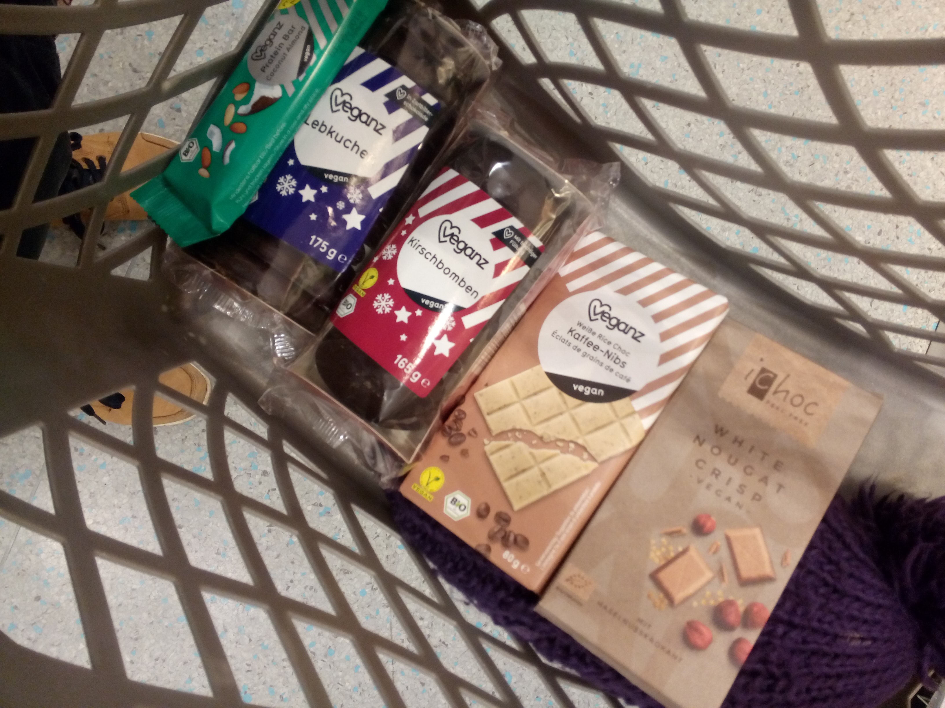 A shopping basket containing vegan cookies and chocolate