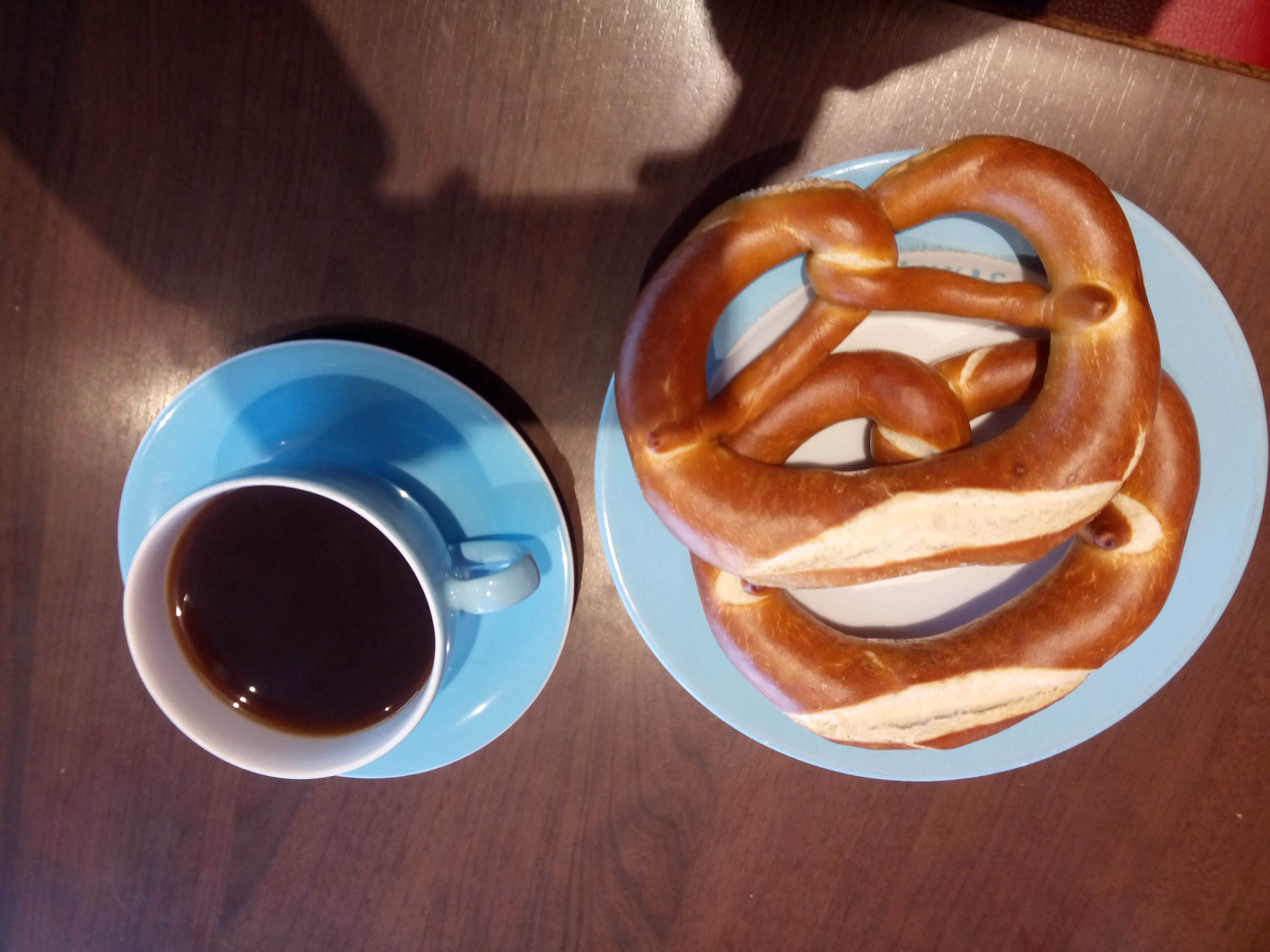 Coffee in a blue cup, and two pretzels on a plate