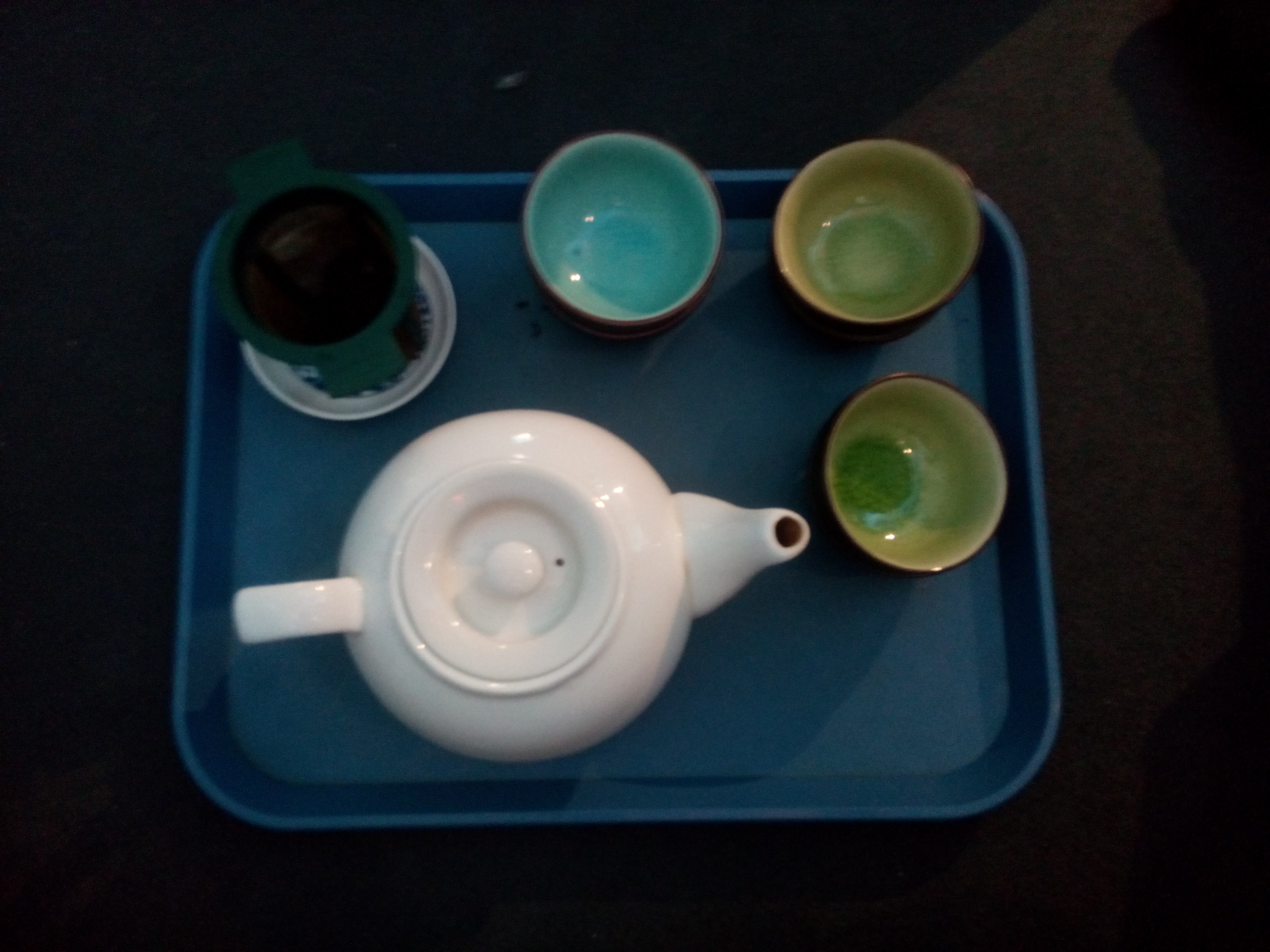 A blue tray with a white teapot, strainer, and three green/blue cups, from above
