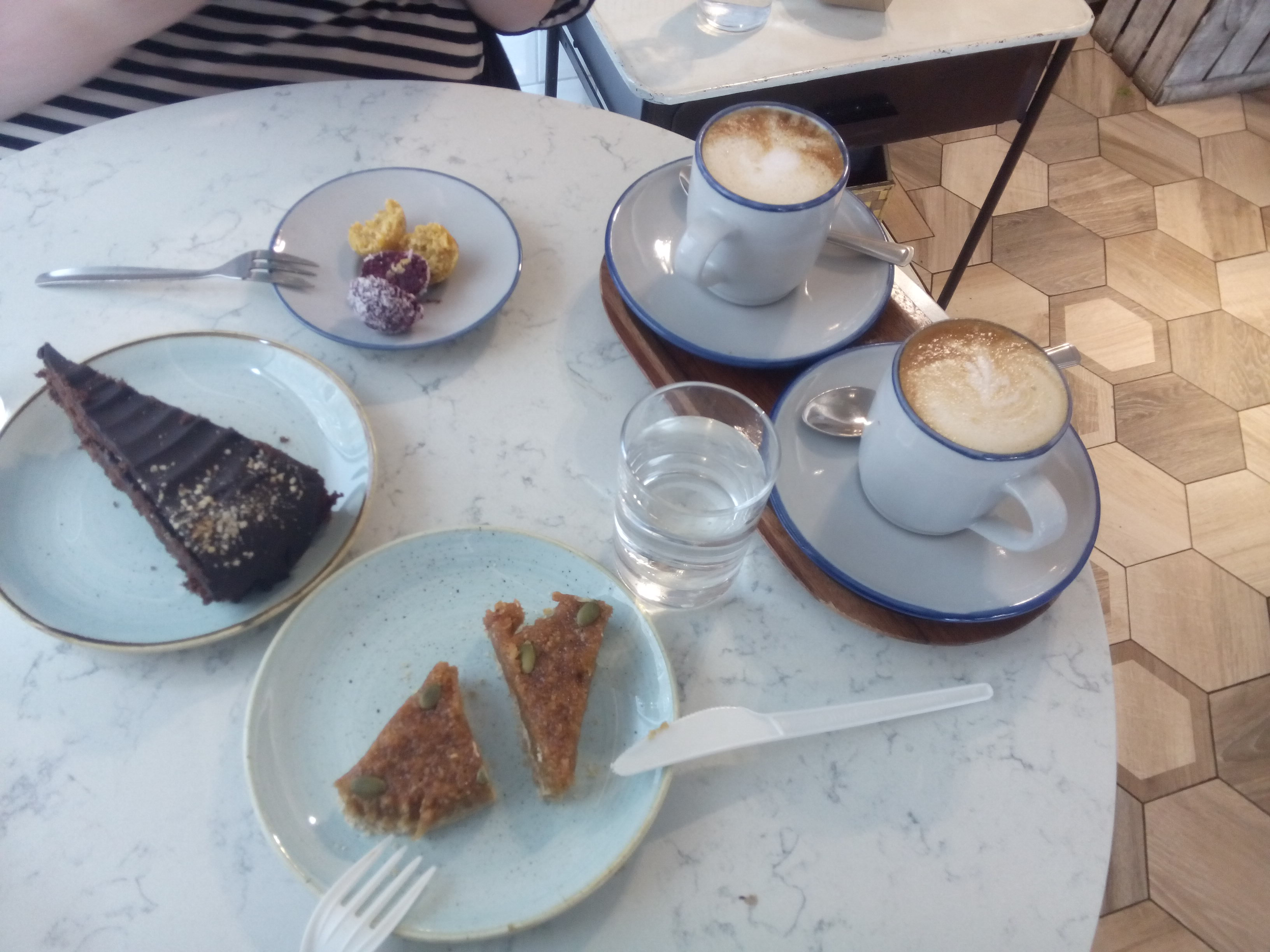 A table covered in plates of cake and two big cups of coffee
