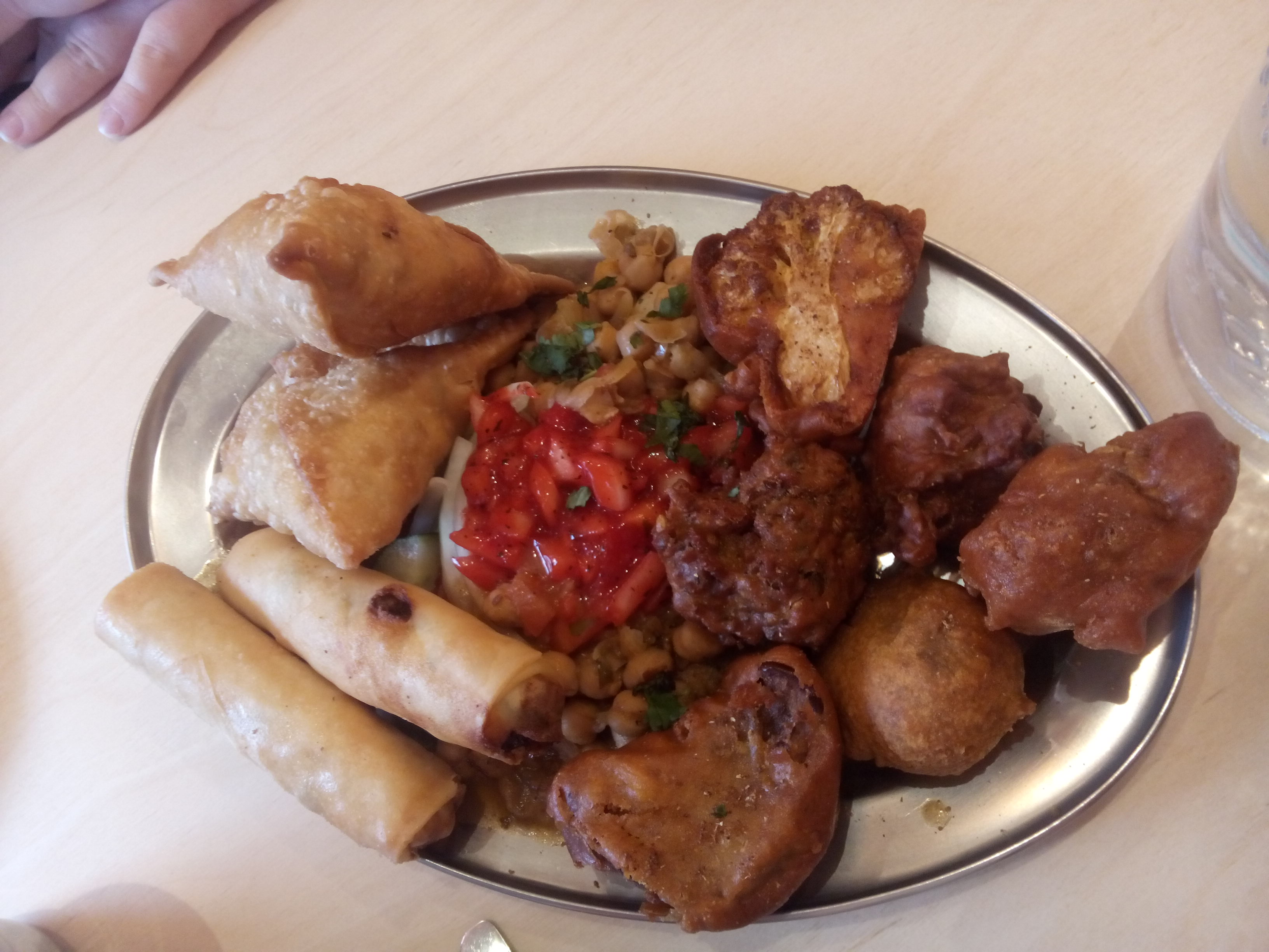A plate full of various pakoras and spring rolls and stuff