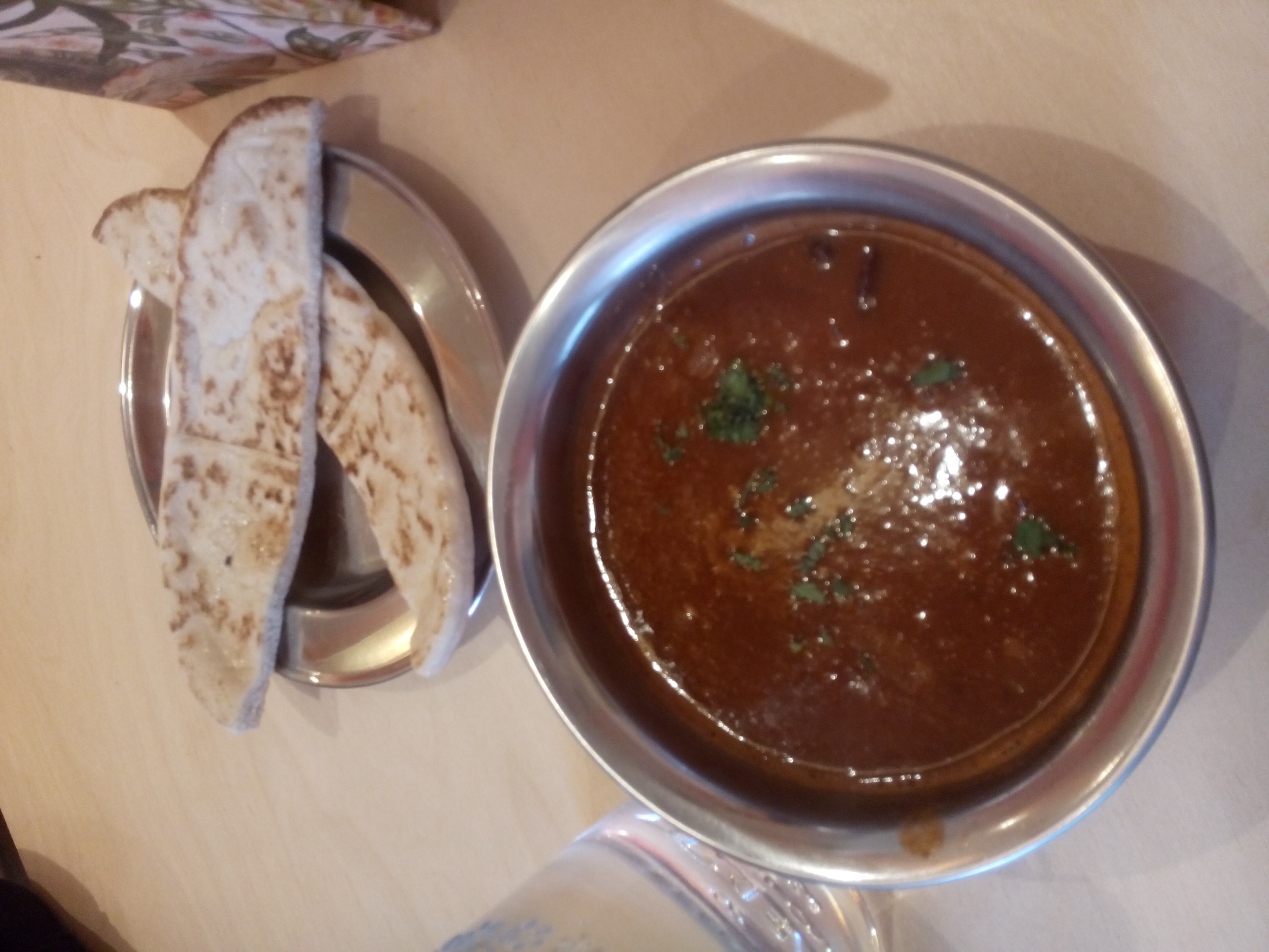 A bowl of red soup with flatbread on a plate