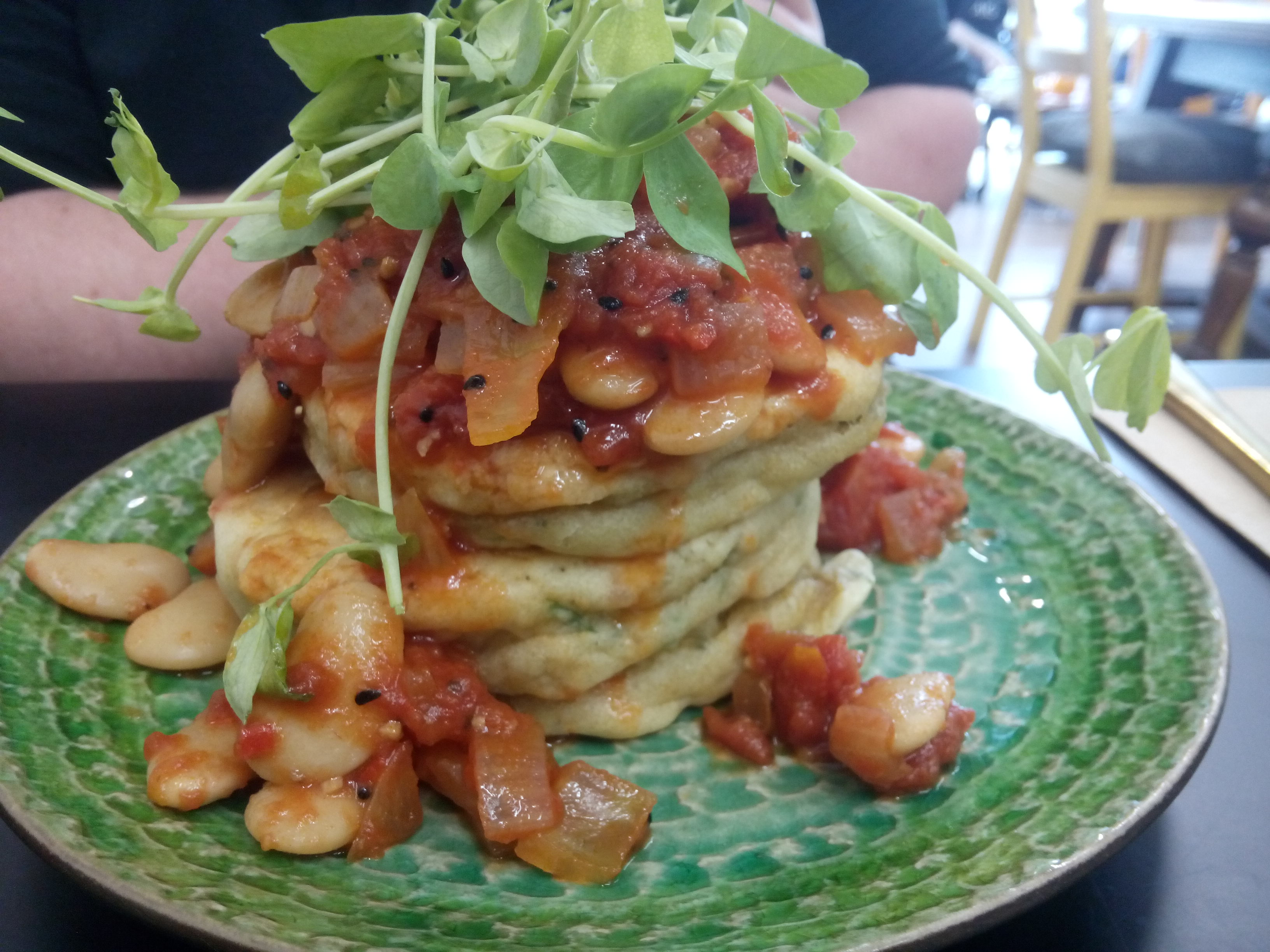 A fat pancake stack with beans in red sauce