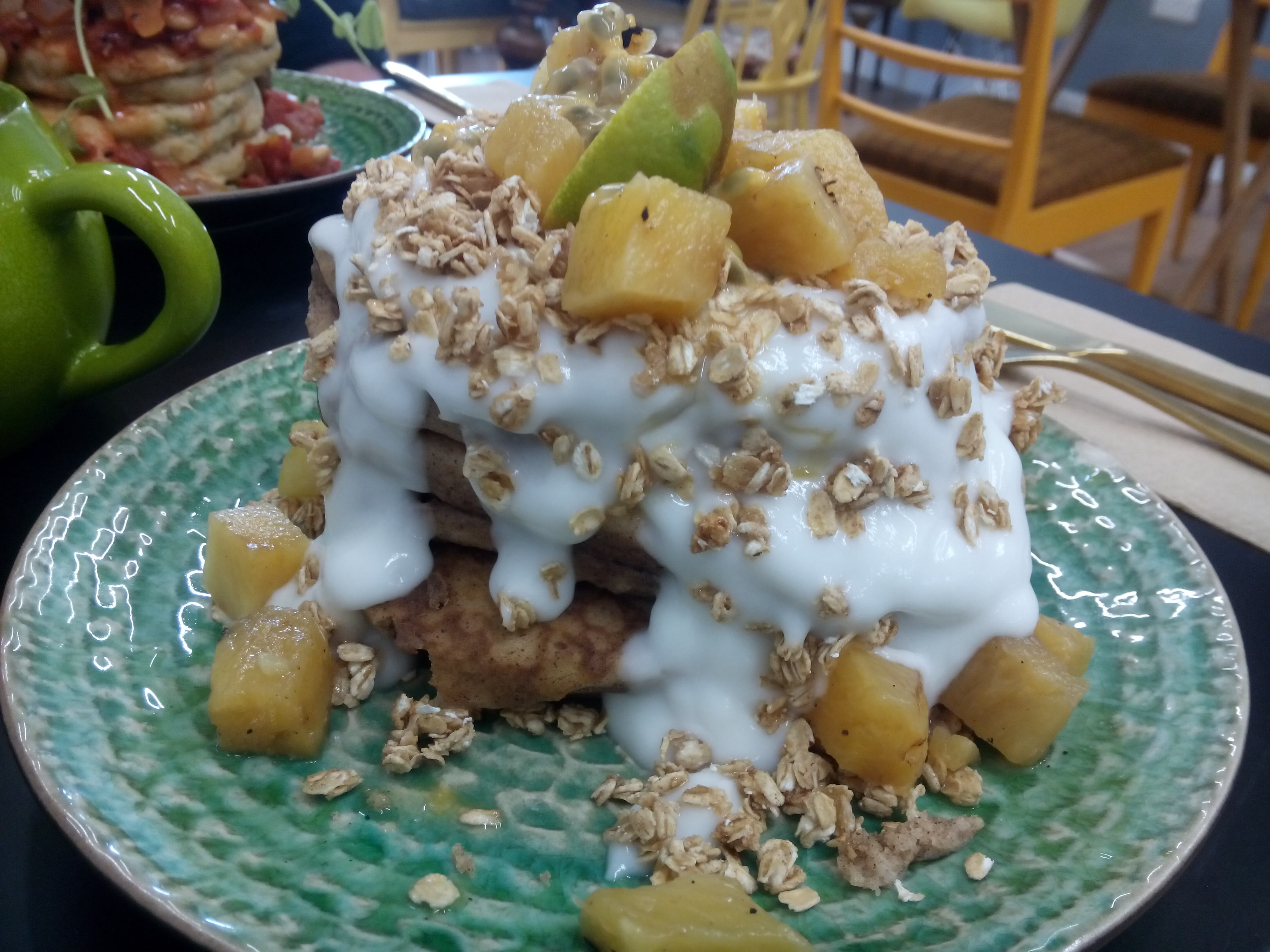 A fat pancake stack covered in coconut yoghurt and yellow fruits