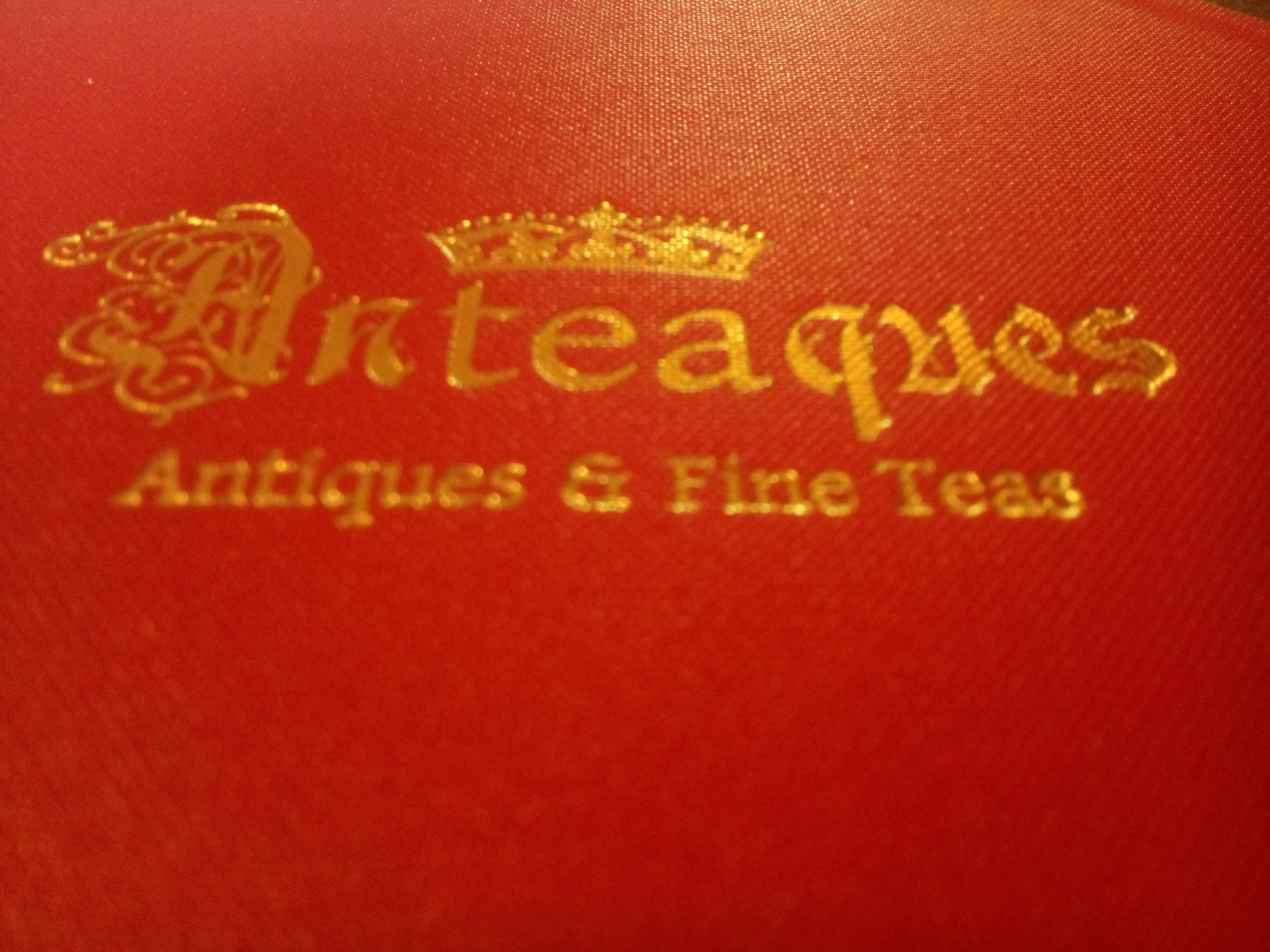 A red fabric menu with 'Anteaques' in gold inlay