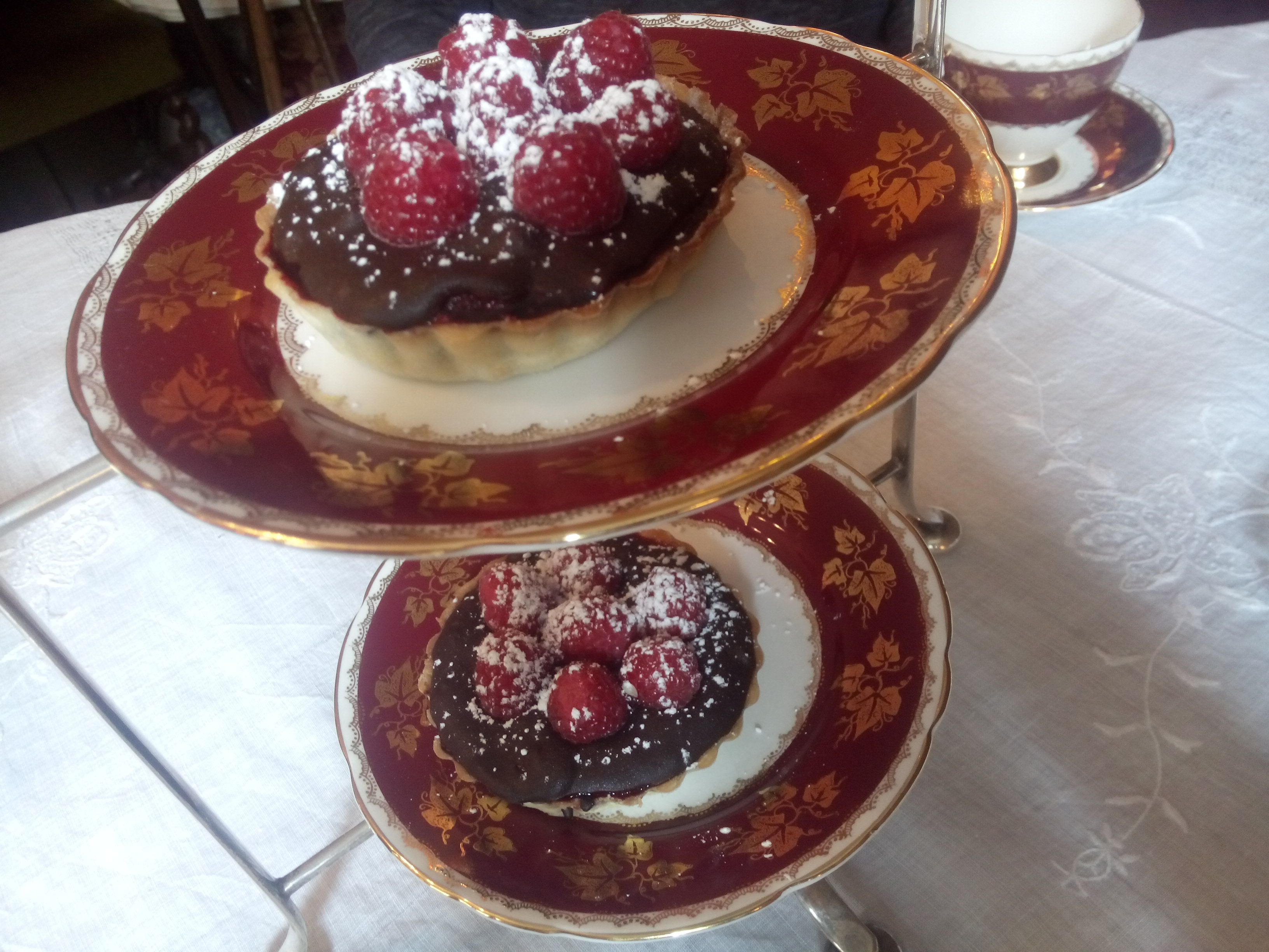 Chocolate and raspberry tarts on a stacked plate