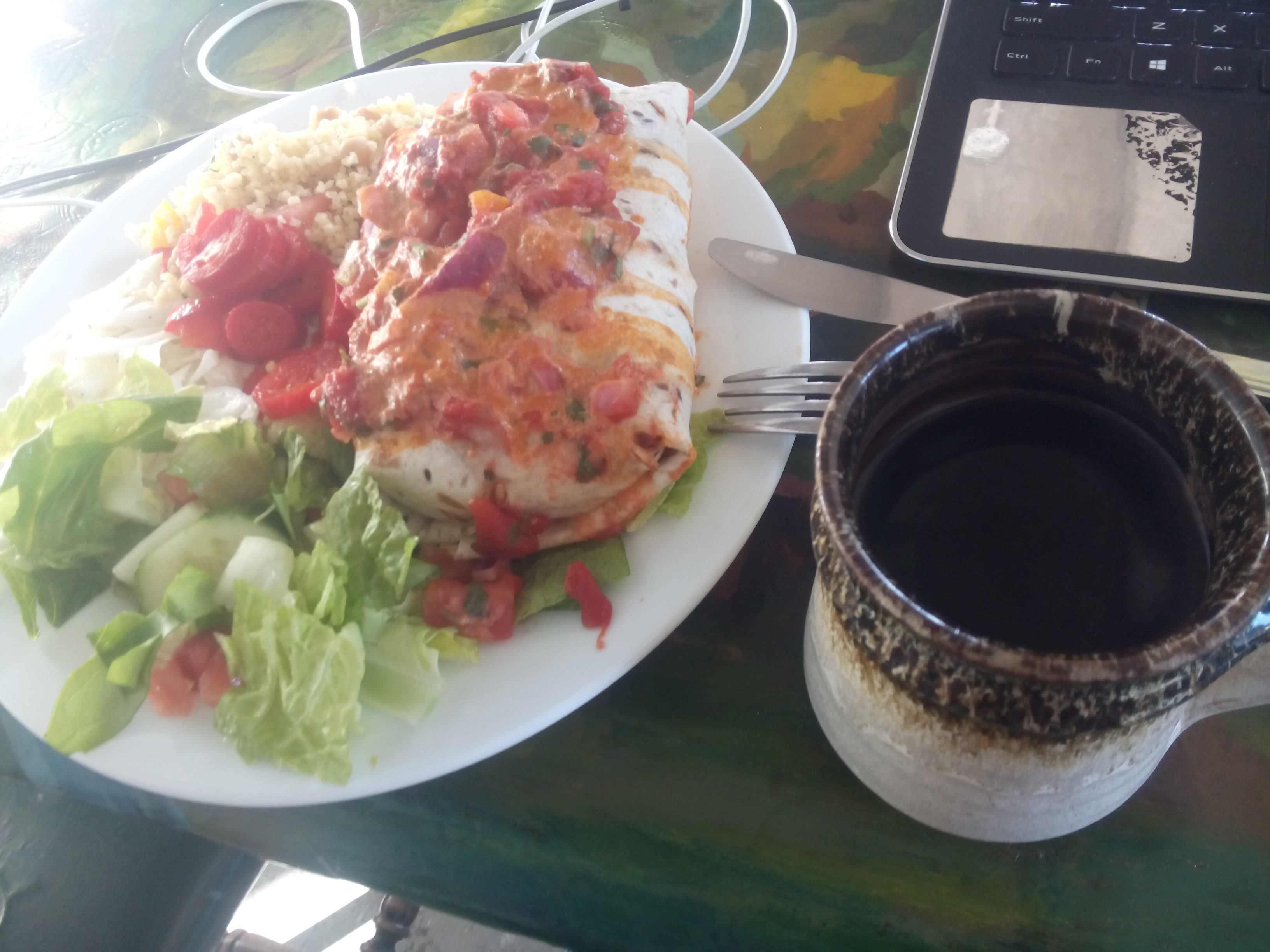 A burrito on a plate smothered in sauce with side salad; a black coffee to the right, and the corner of a laptop keyboard