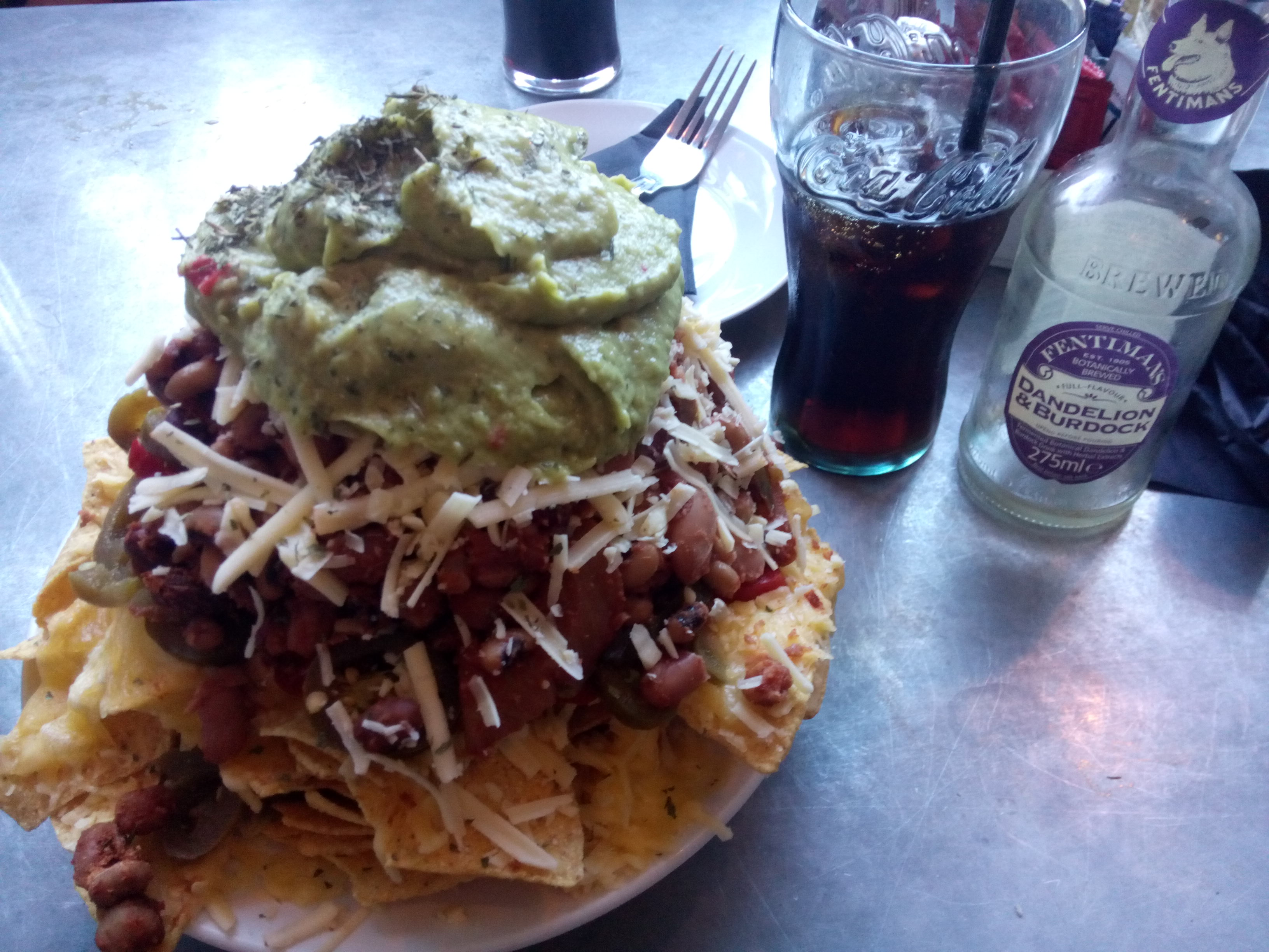An enormous pile of nachos indispersed with vegan cheese, bean chilli, jalapenos and guacamole