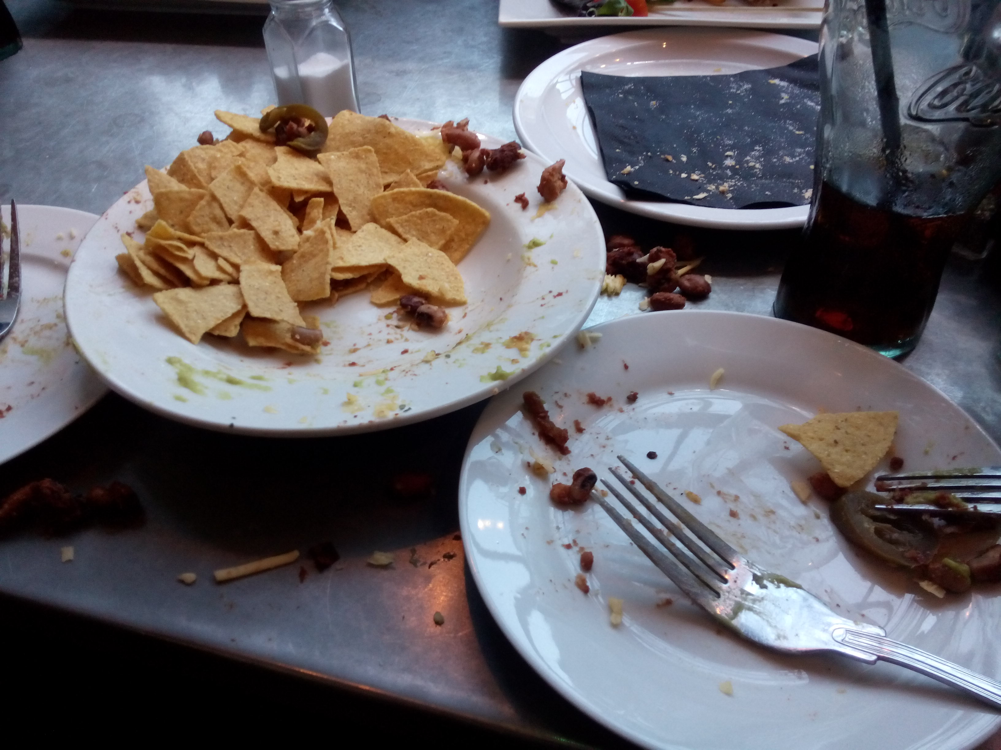 A couple of white plates with leftover tortilla chips and the odd jalapeno. Some beans on the table.