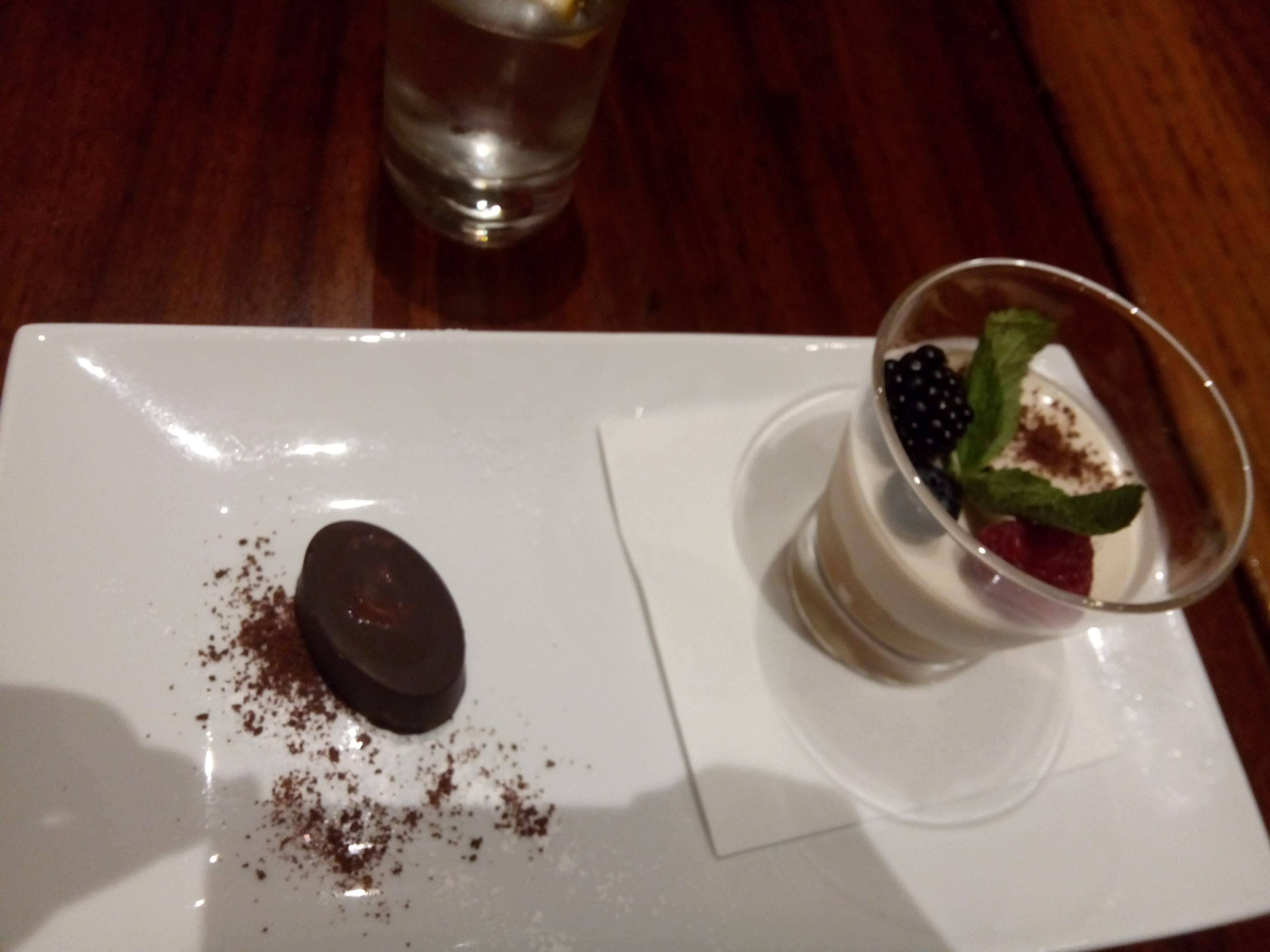 A creamy dessert in a glass alongside a chocolate on a plate