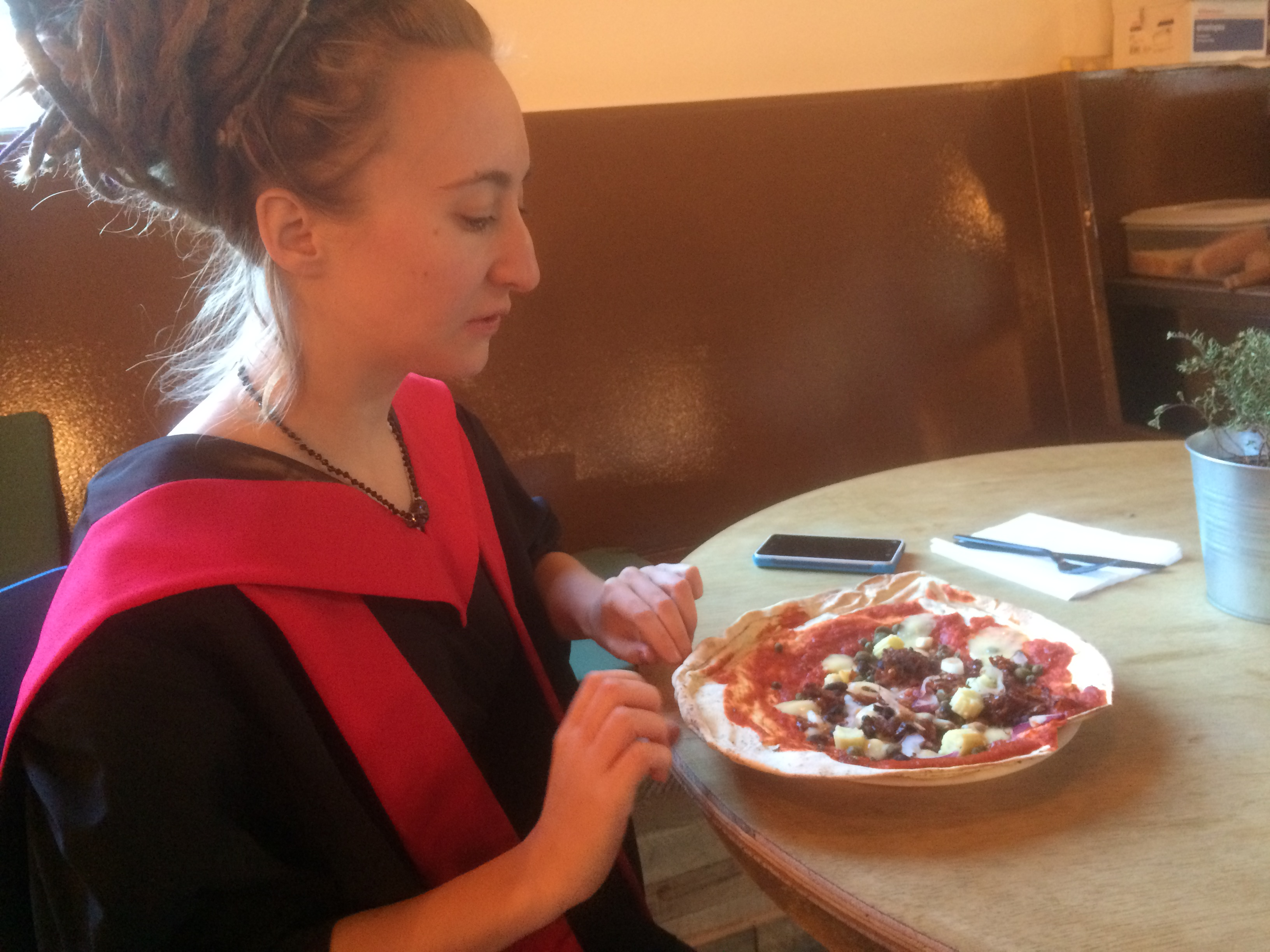 rhiaro in graduation robes sneaks up on unsuspecting flatbread