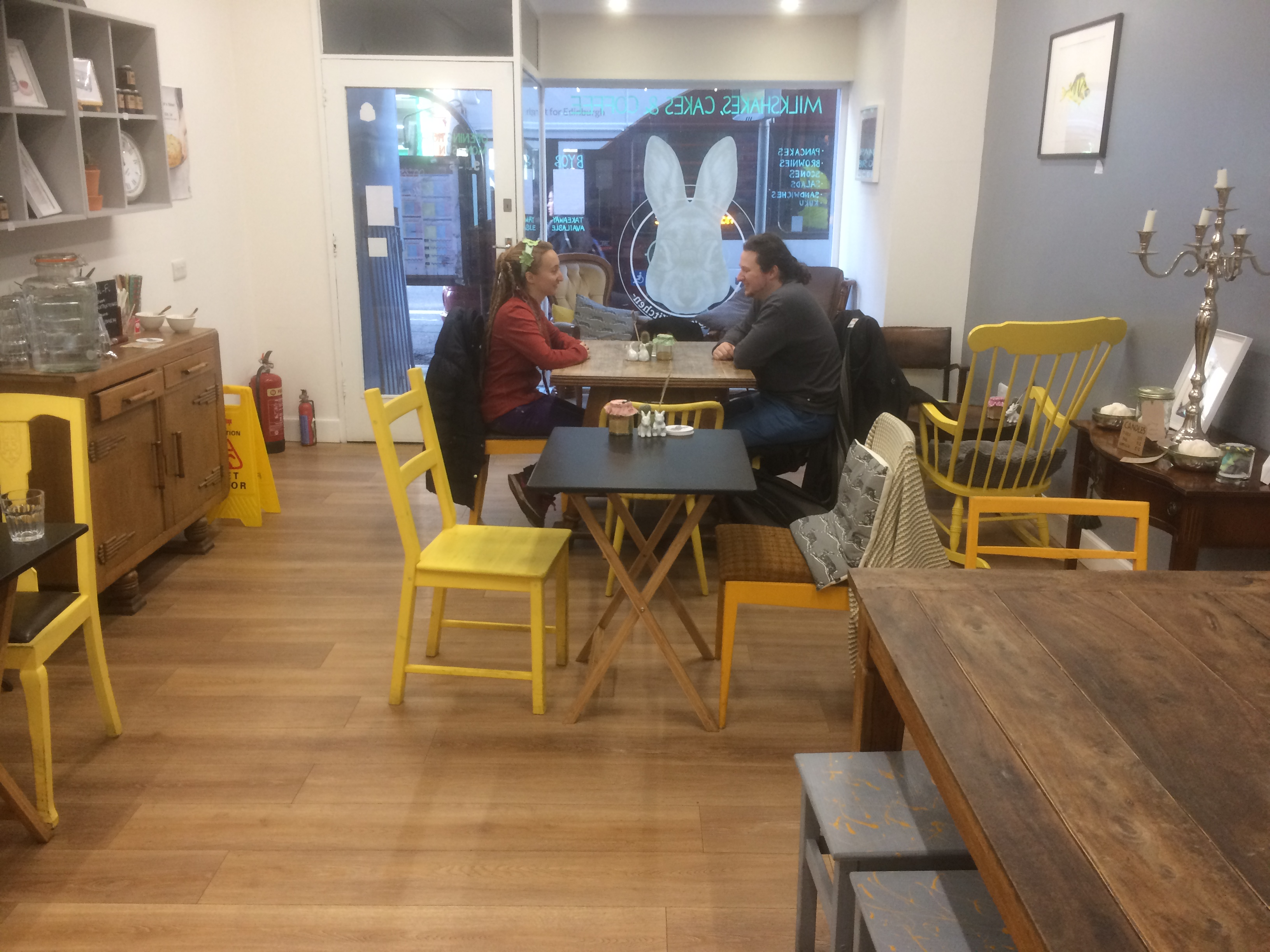 A cafe interior with a wooden floor, yellow chairs, and two people at a table