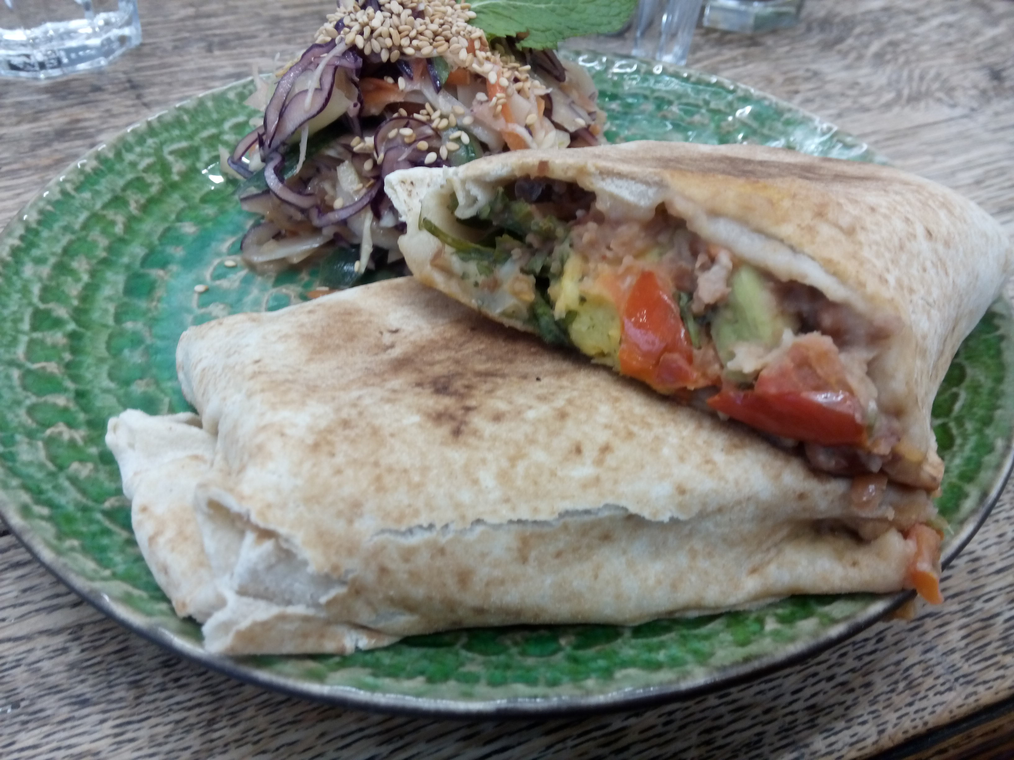 A wrap stuffed with filling on a plate with salad in the background