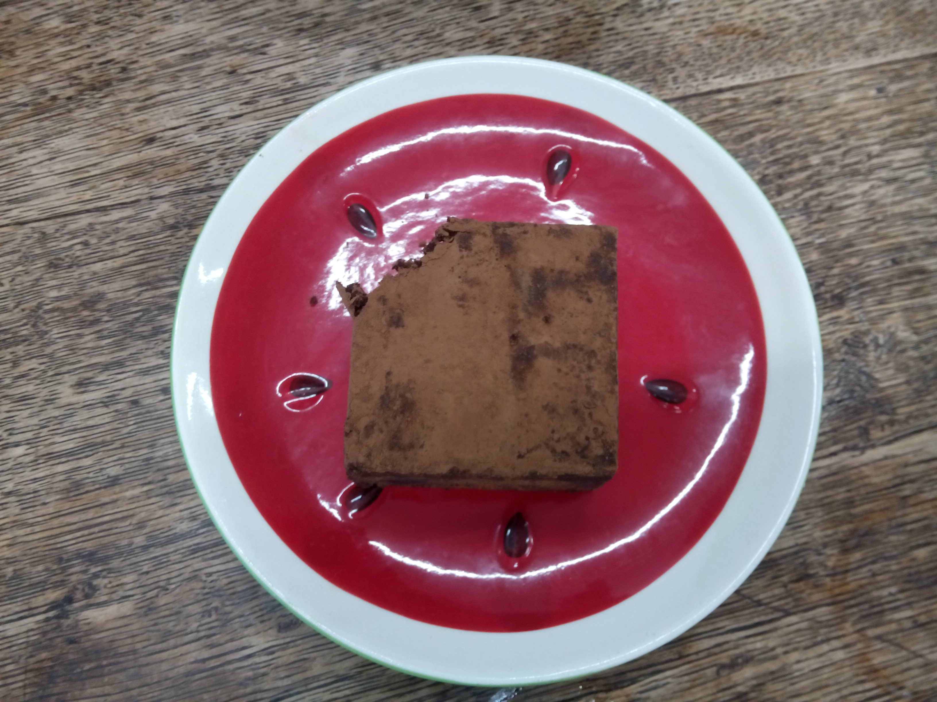 A dark chocolate square cake on a red plate