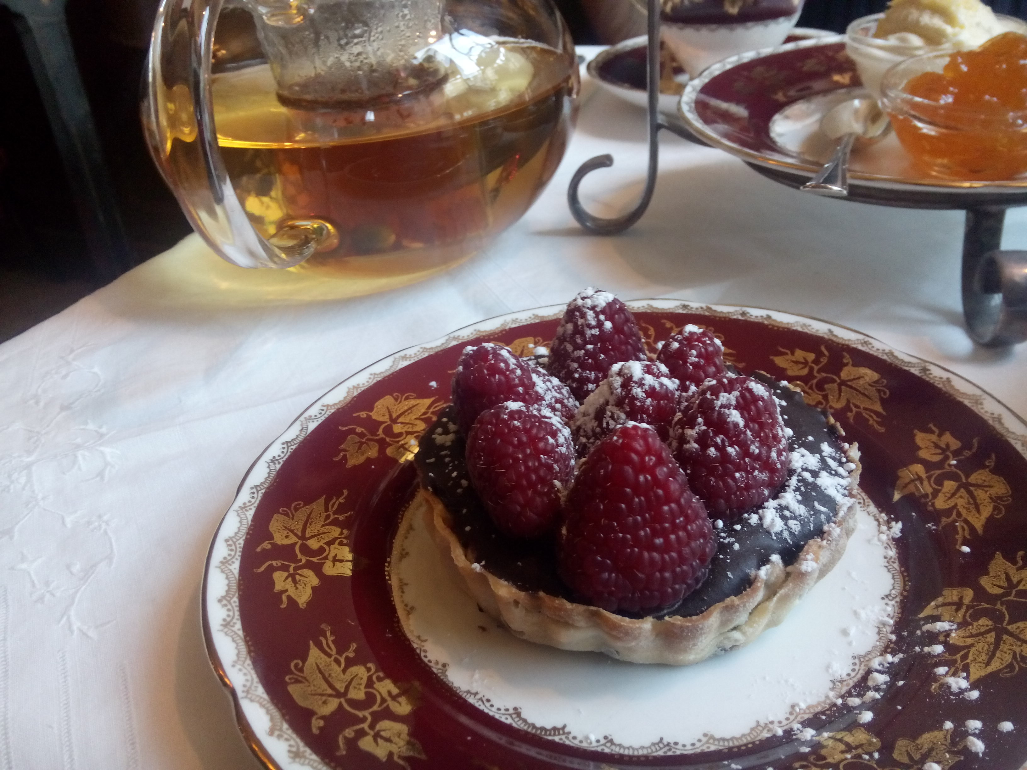 A choclate and raspberry tart on a plate, with a glass teapot half full in the background