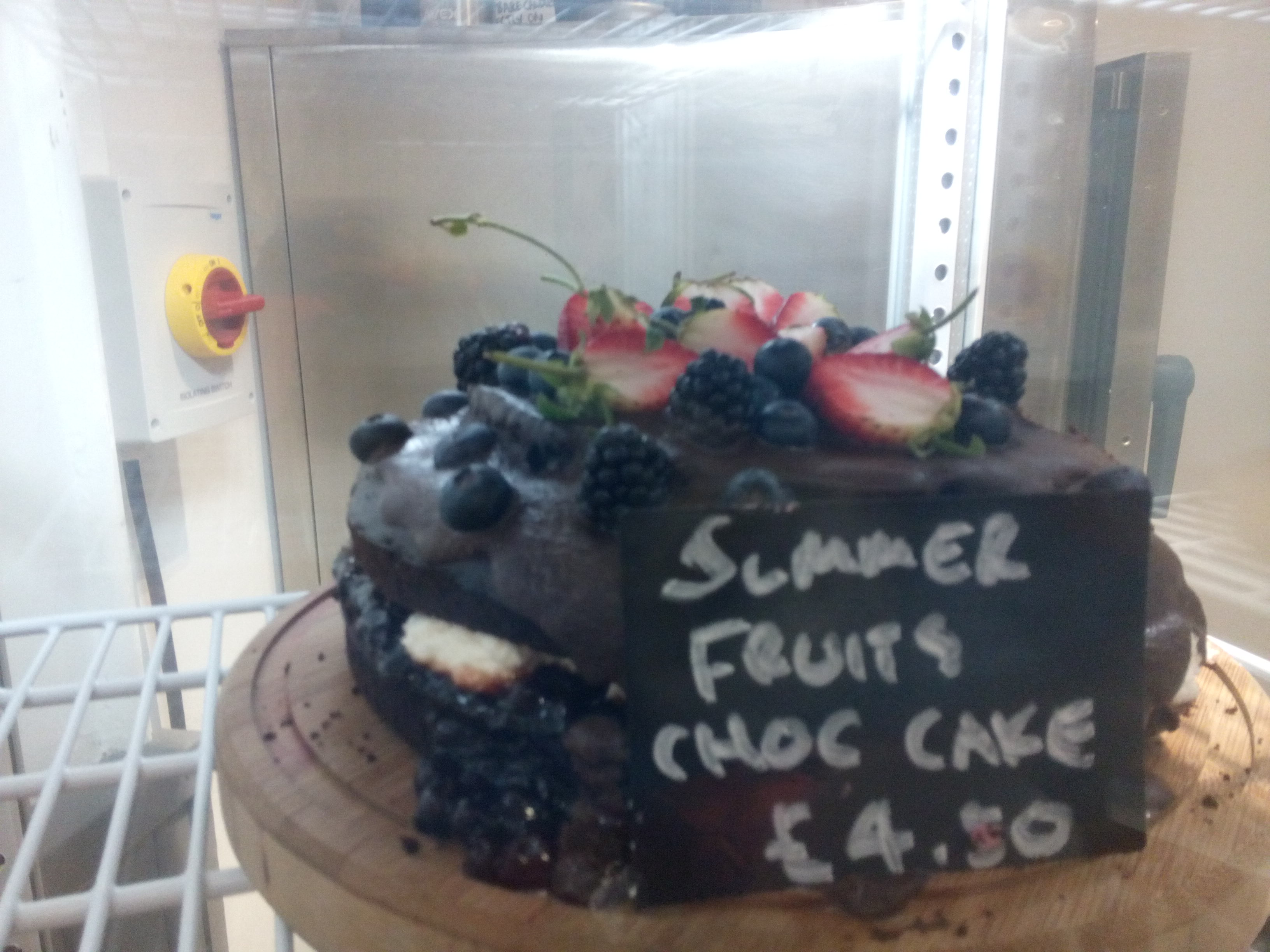 Chocolate summer fruits cake behind glass
