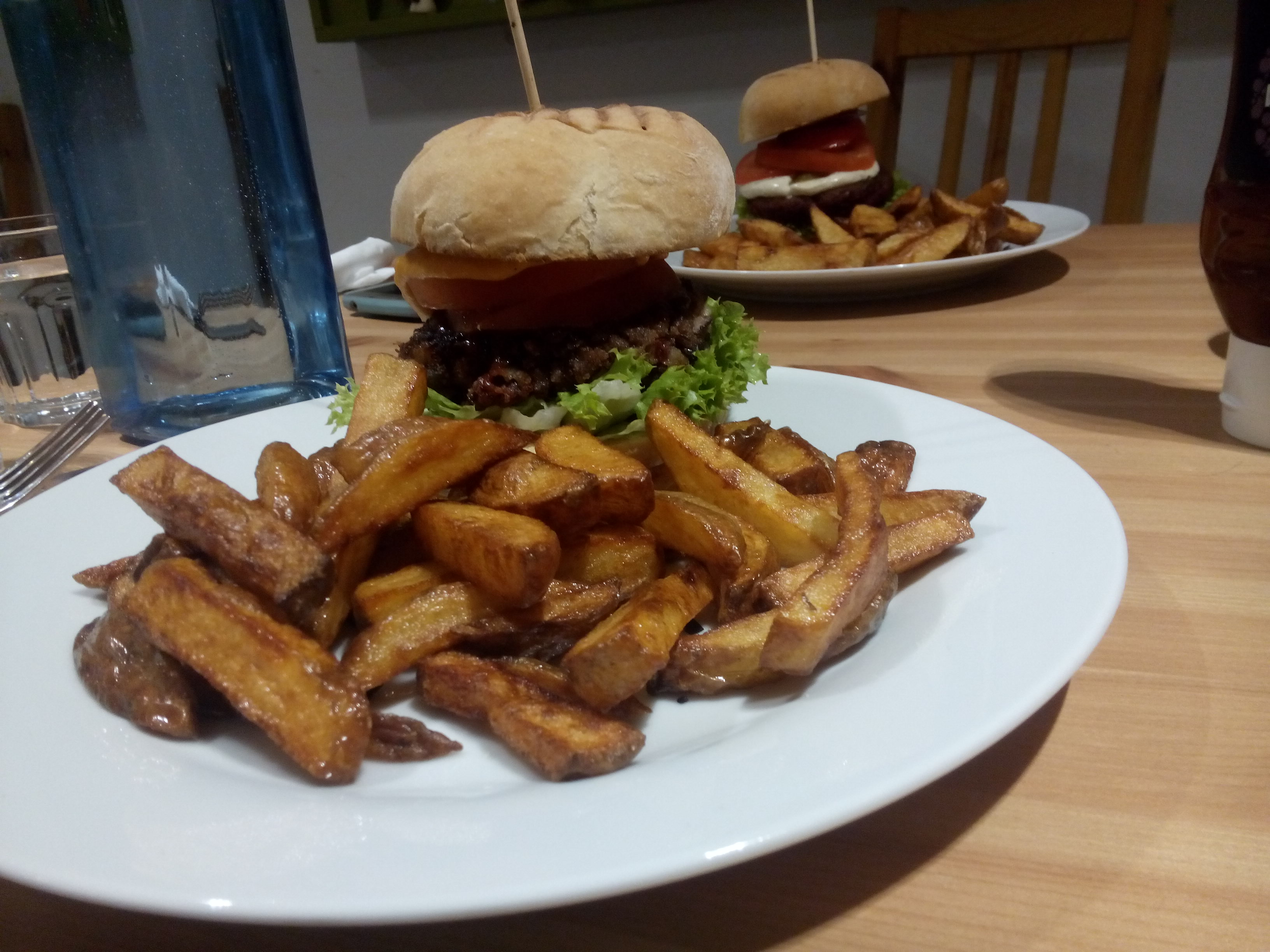 A towering burger in the foreground on a white plate, accompanied by chips. A similiar one in the background