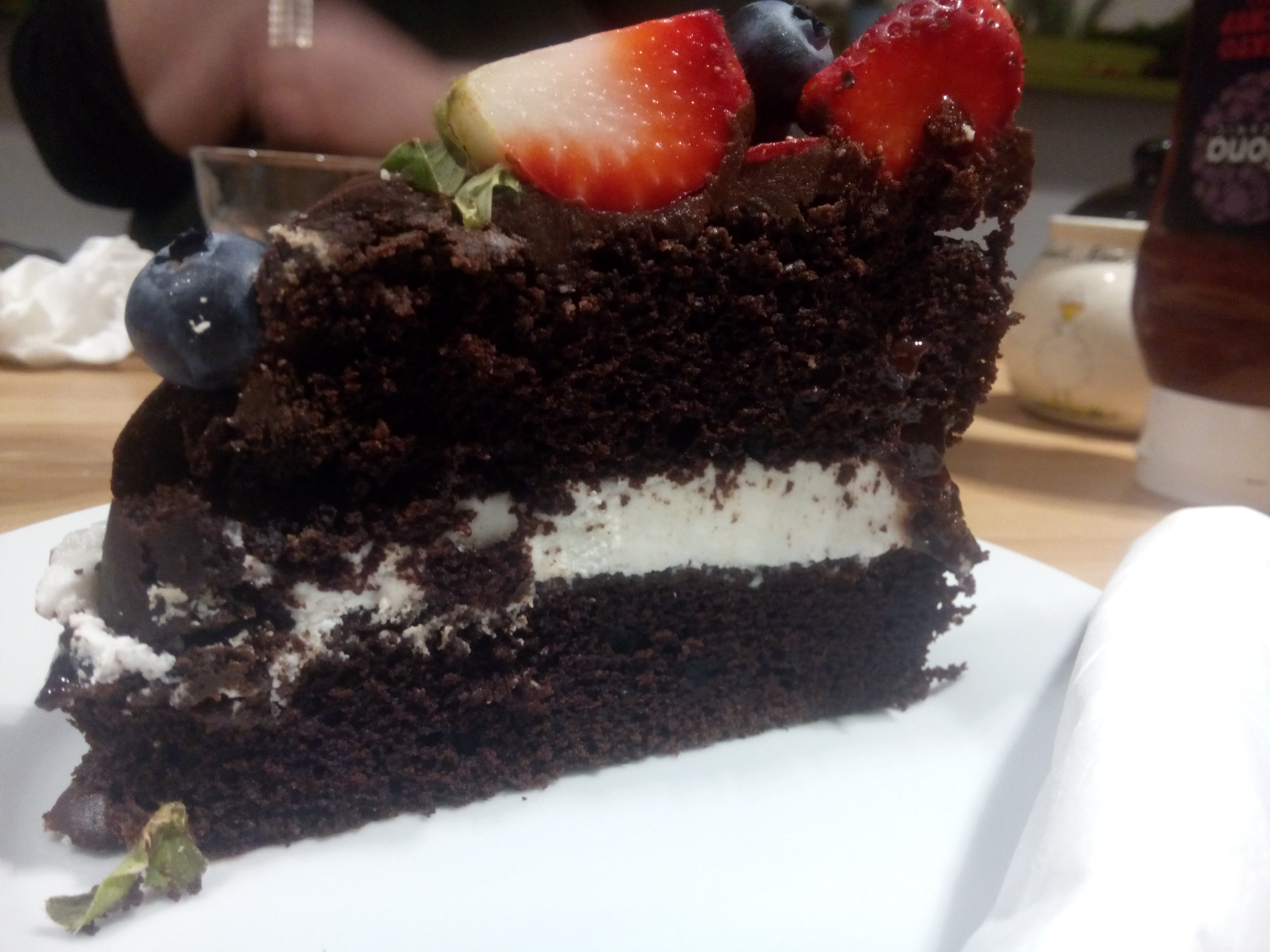Chocolate cake with white cream in the middle and strawberries and blueberries on top
