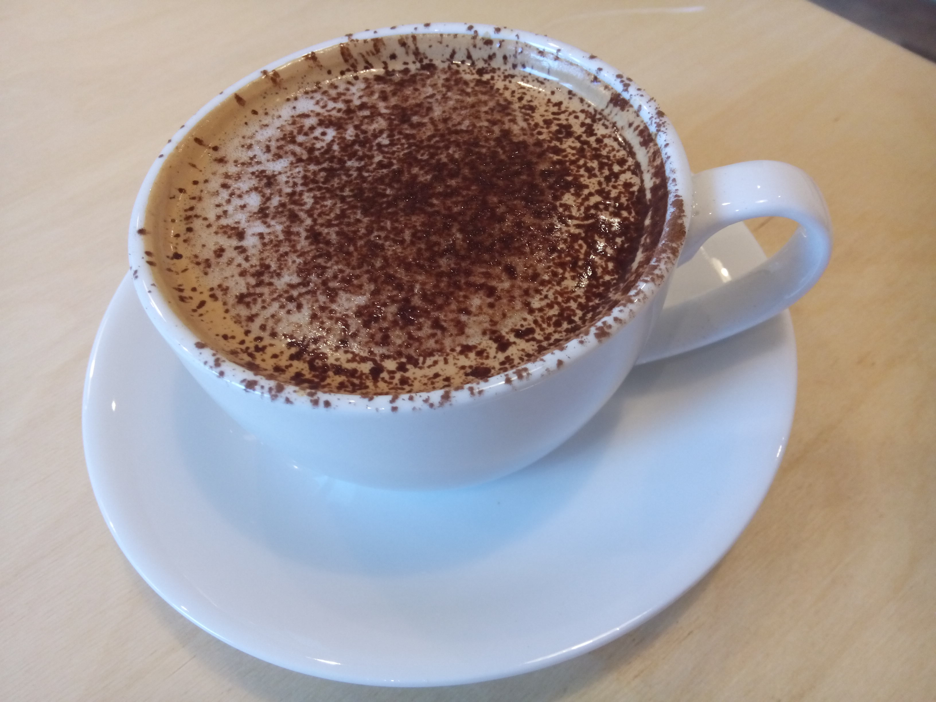 A white cup and saucer with chocolate sprinkled foamy coffee