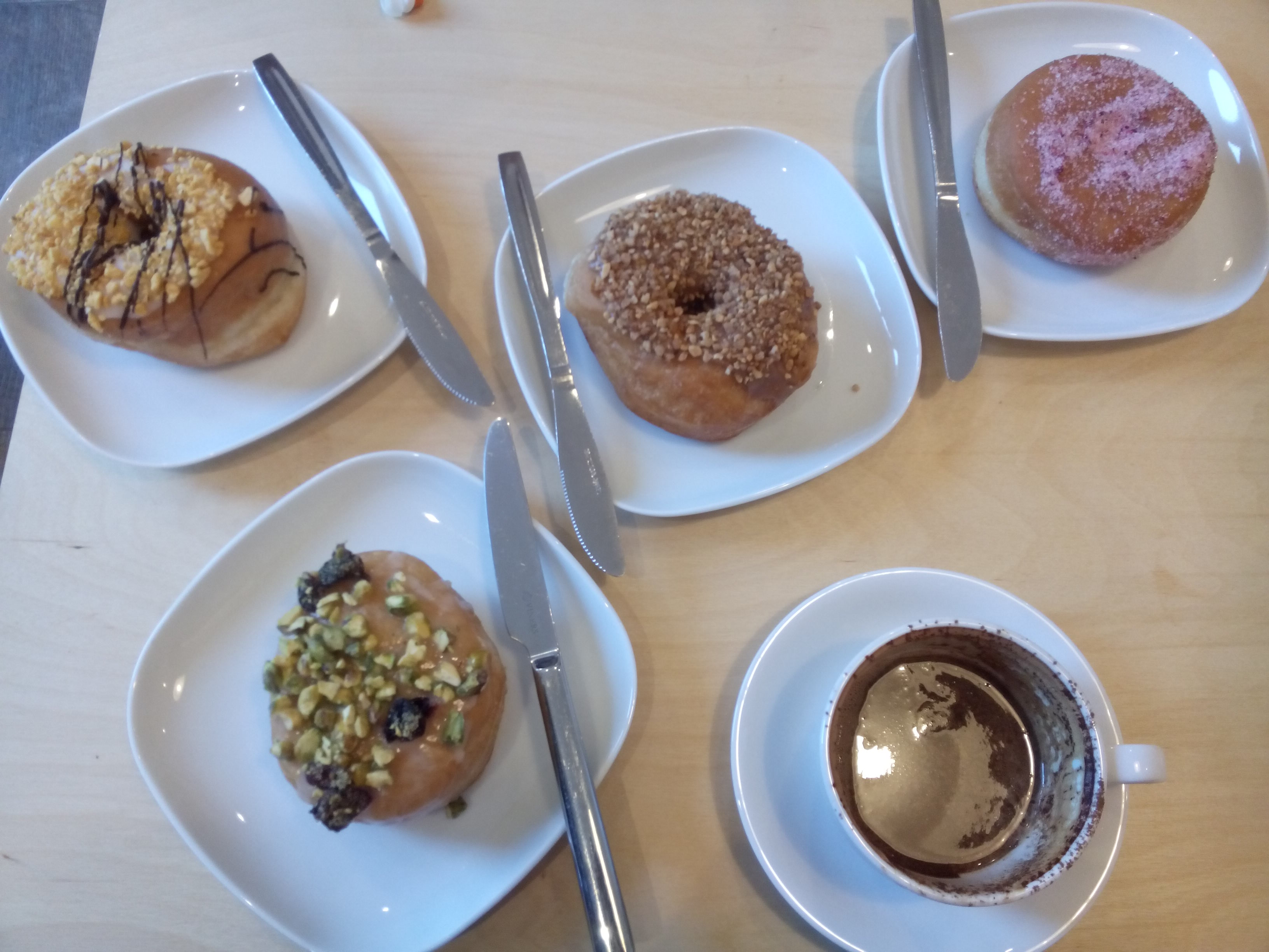 Four square white plates with doughnuts, and one cup of coffee, from above