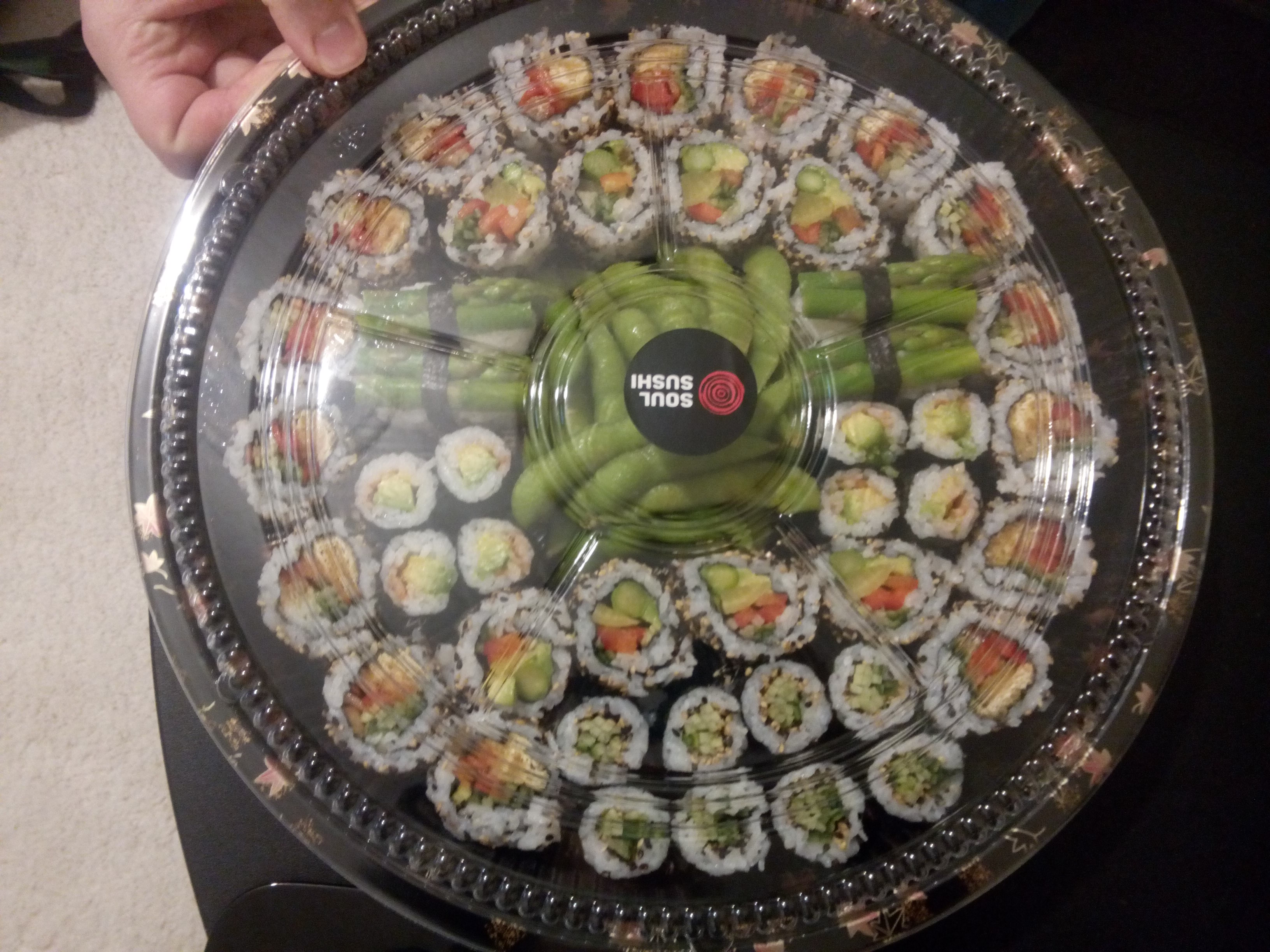 A round plastic tray filled with sushi pieces and edamame in the middle