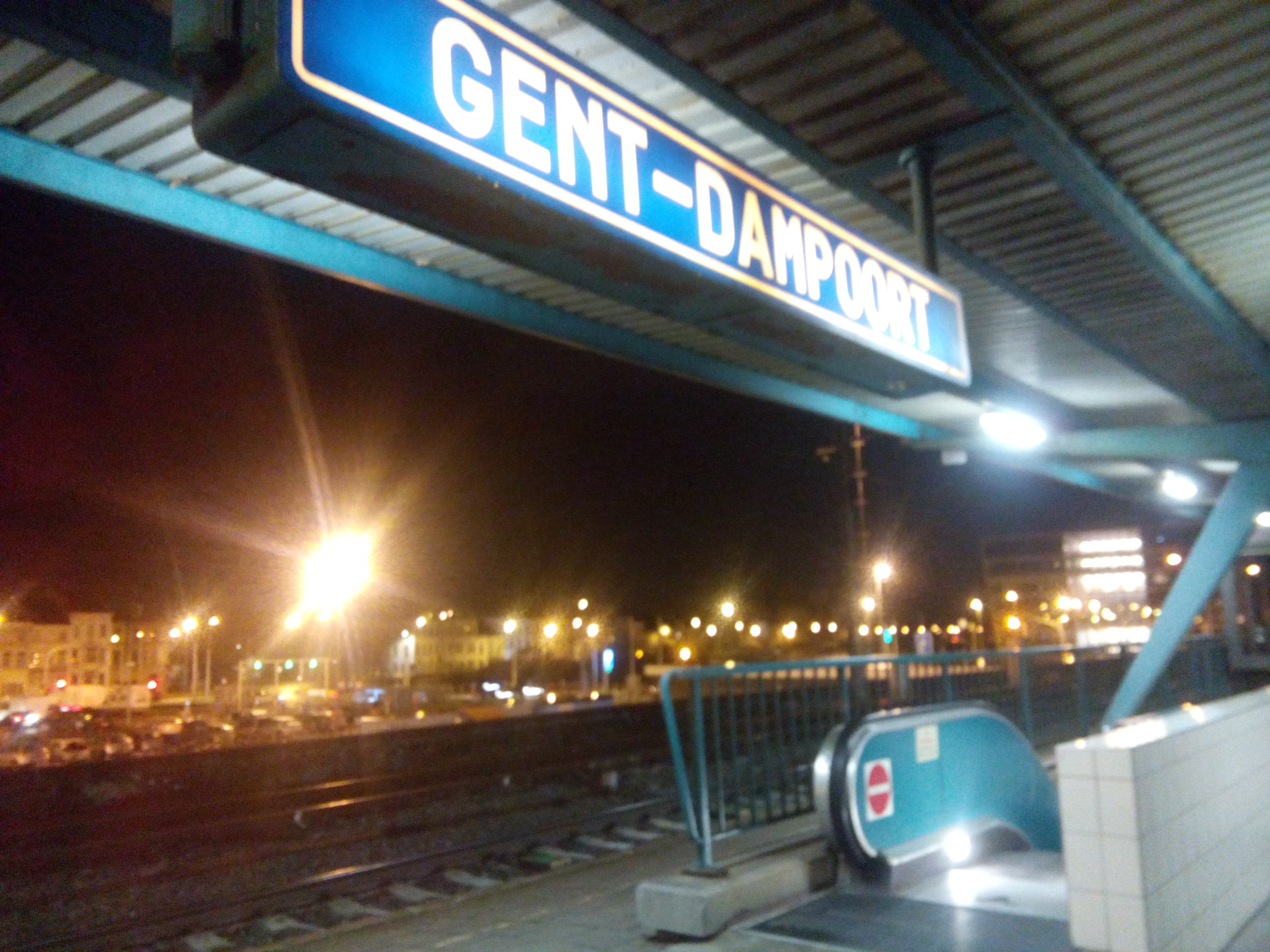 A poorly lit train station sign reading Ghent-Dampoort