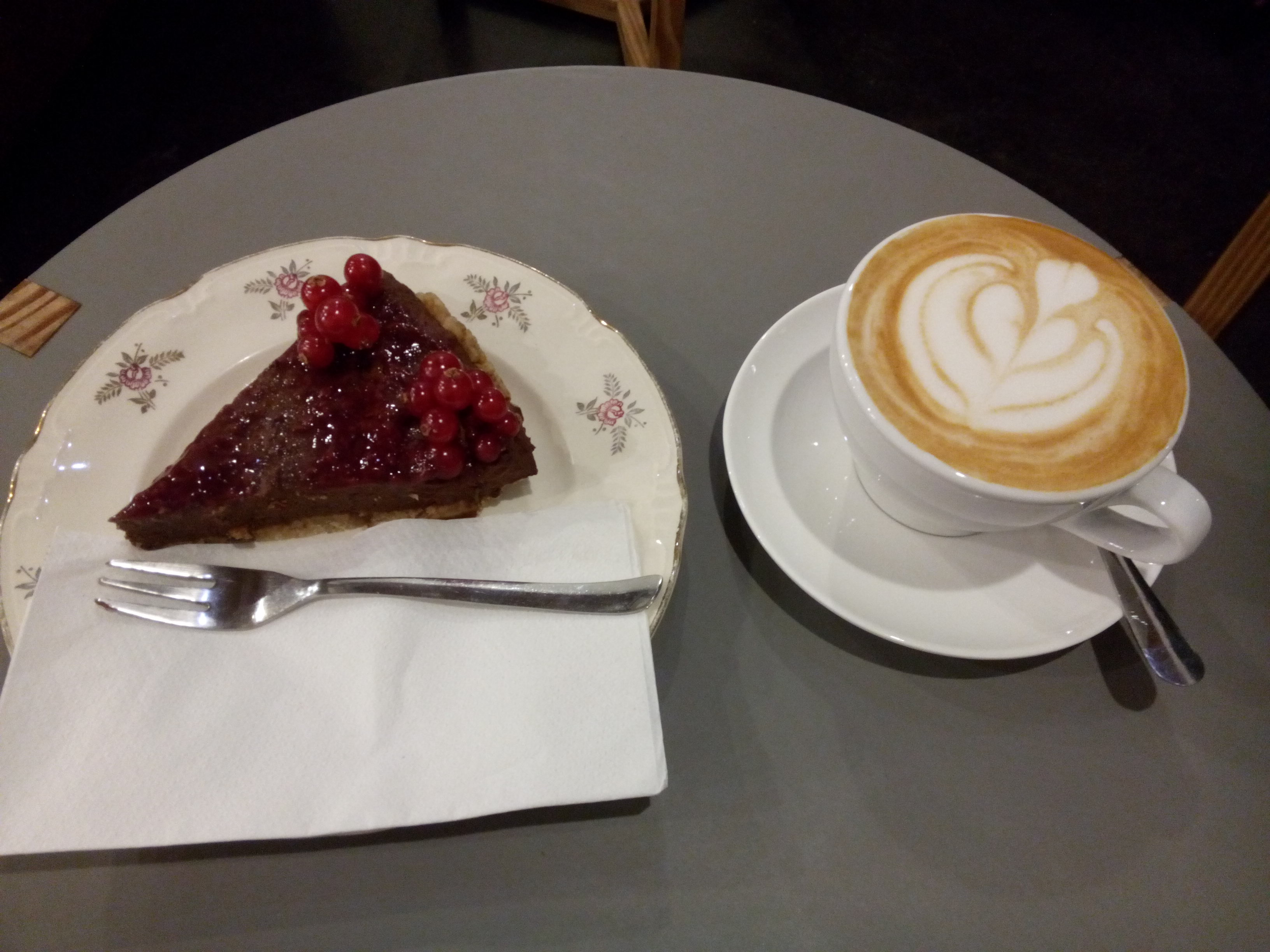 A chocolate pie on a plate, and a cup of foamy flat white coffee on a table
