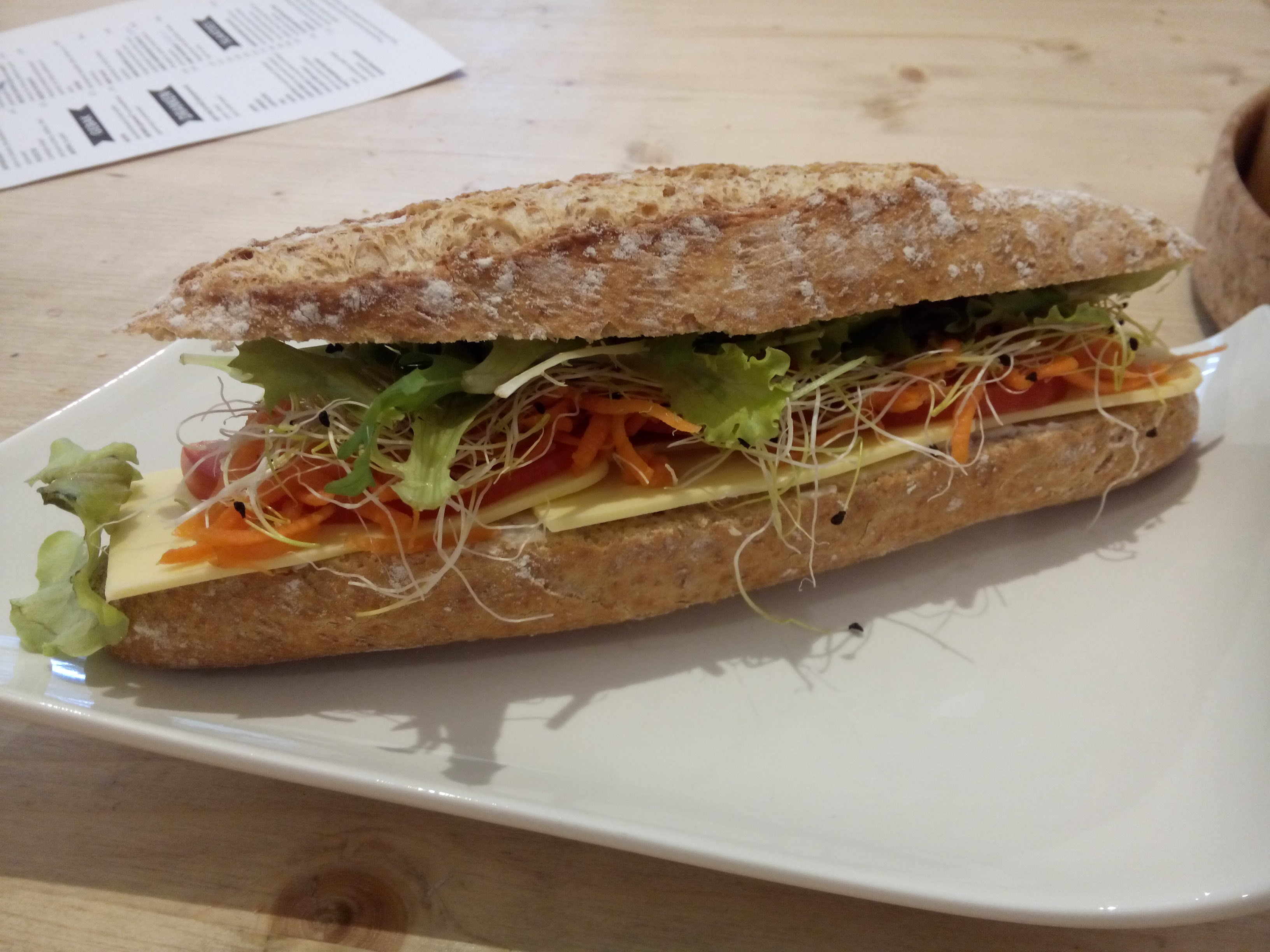 A crusty baguette filled with salad and (vegan) cheese on a plate