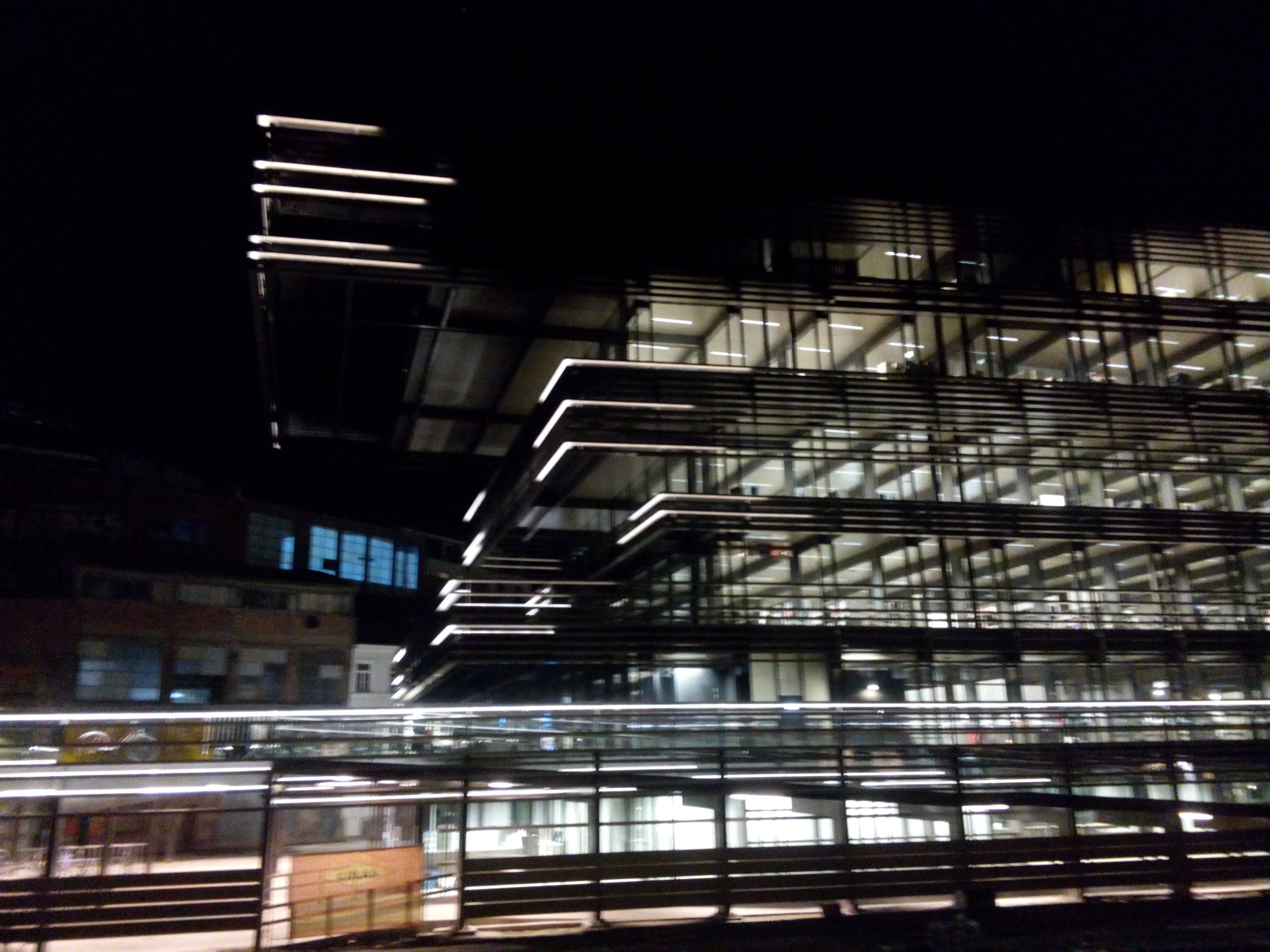 A geometric building in the dark, lit up with lights from inside